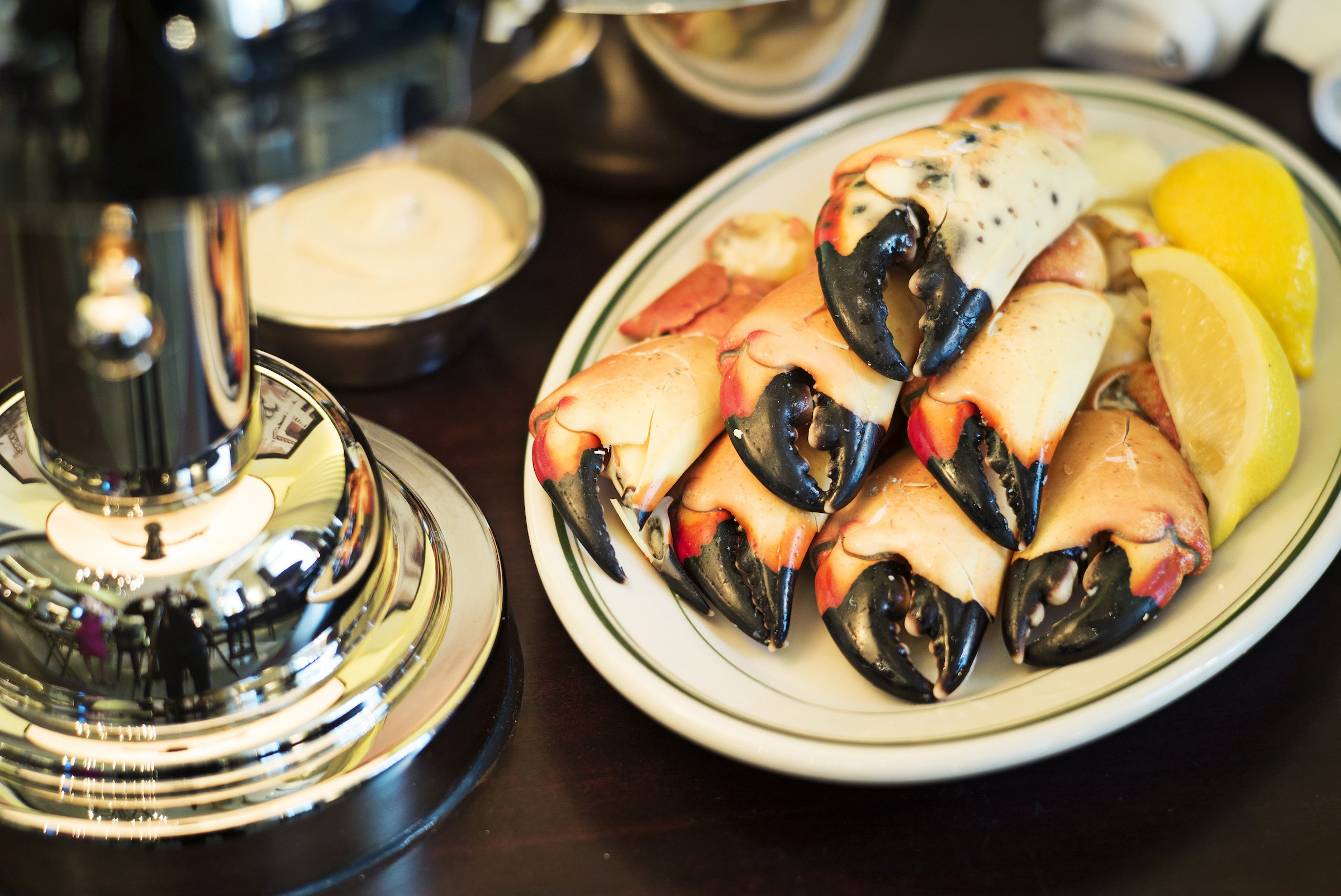 A plate of stone crab claws and two lemon wedges on a plate on a restaurant table.
