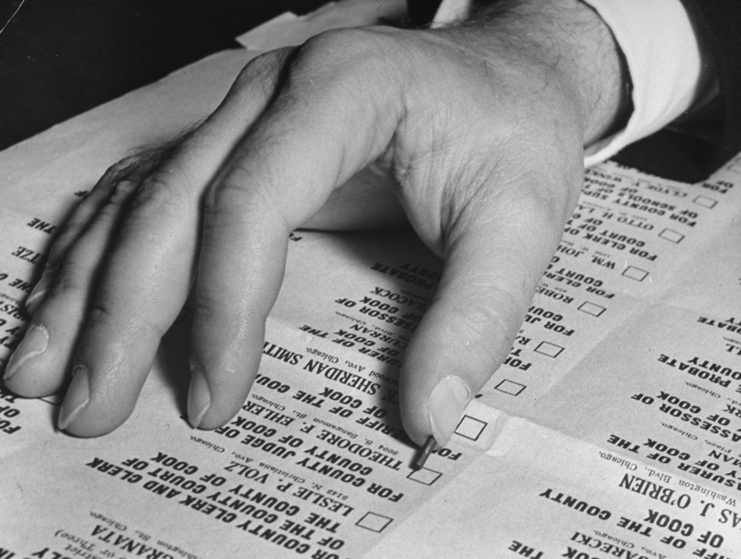 Vintage black-and-white photo of a hand on a paper ballot.