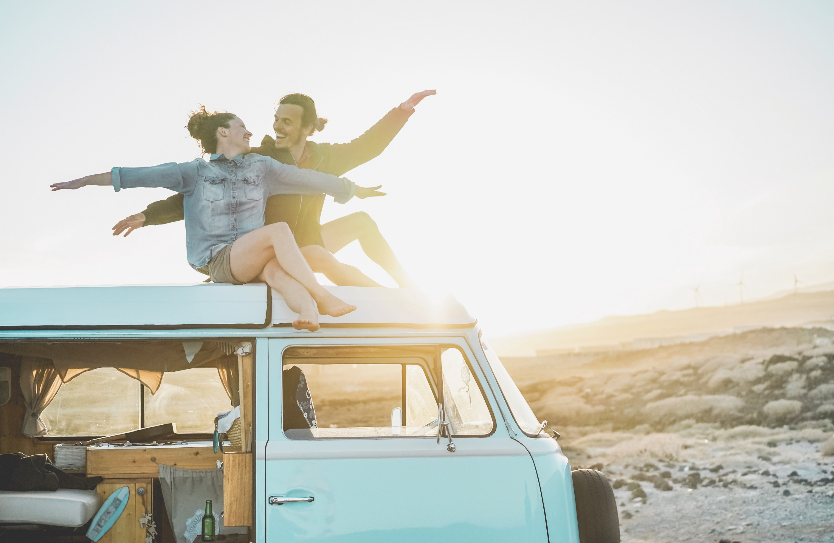 A silly couple sits on top of their van at sunset with their arms spread wide.