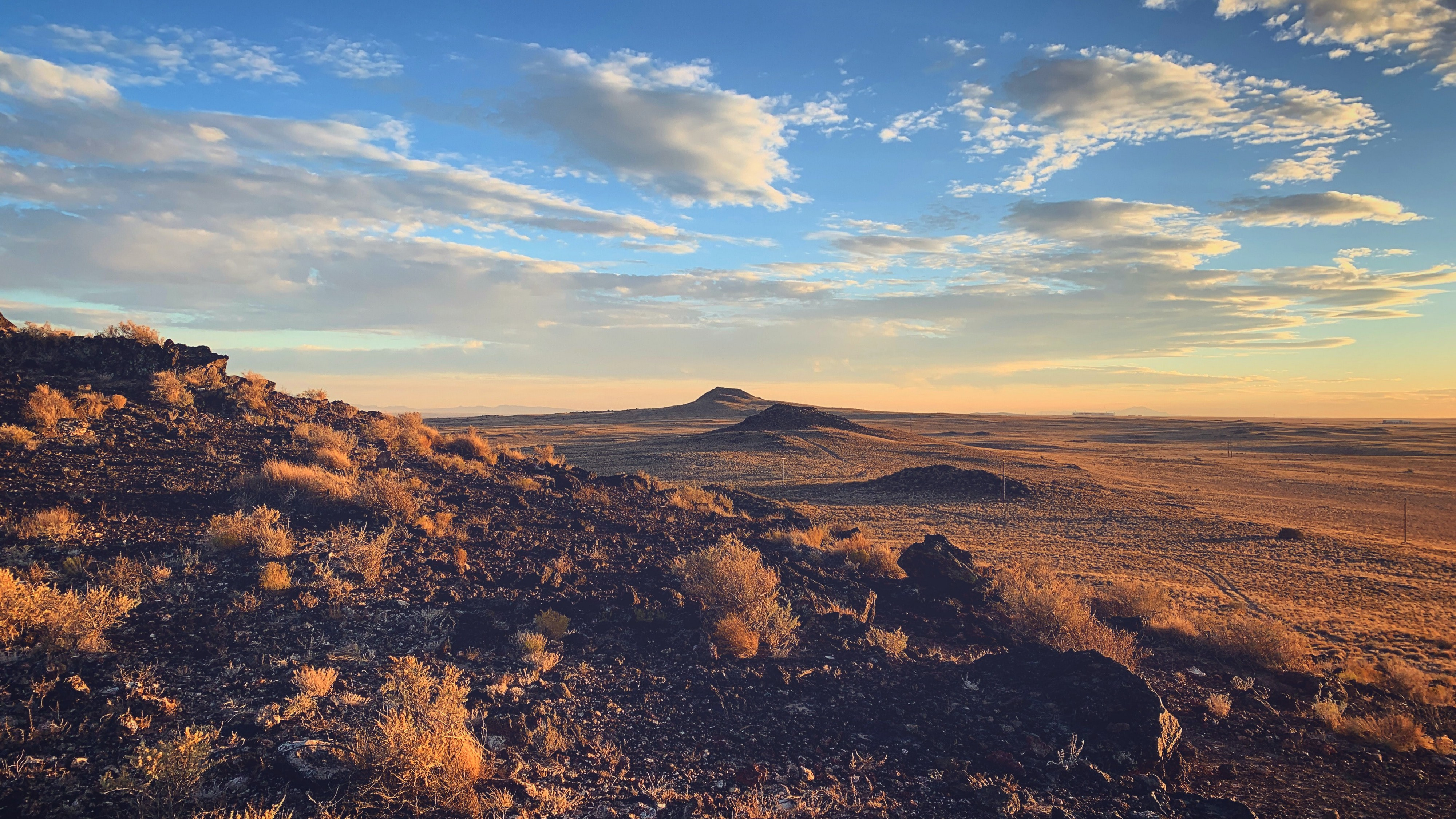 The ancient volcanoes of Petroglyph National Monument sit dormant as the setting sun paints the surrounding desert golden.