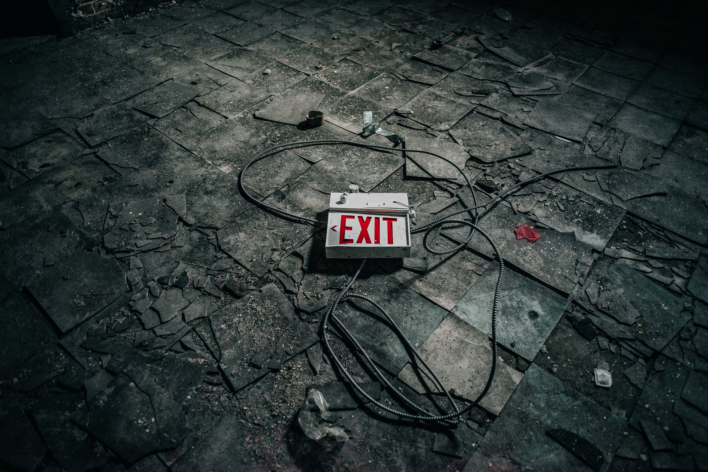 "A destroyed red ""EXIT"" sign with loose wires laying on a burned tile floor."