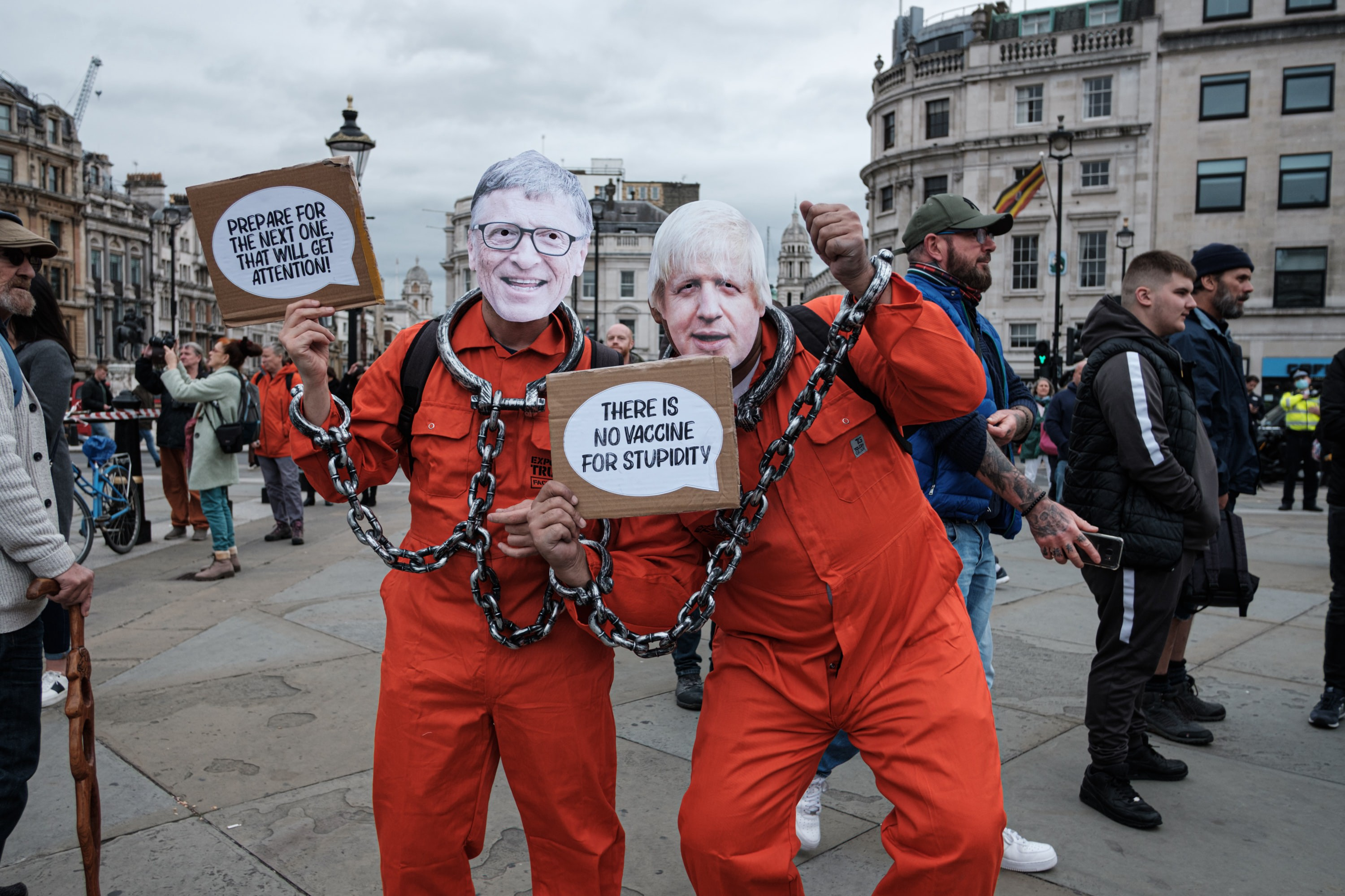 Two people in orange jumpsuits, fake shackles and masks of Boris Johnson and Bill Gates protest against COVID-19 restrictions.