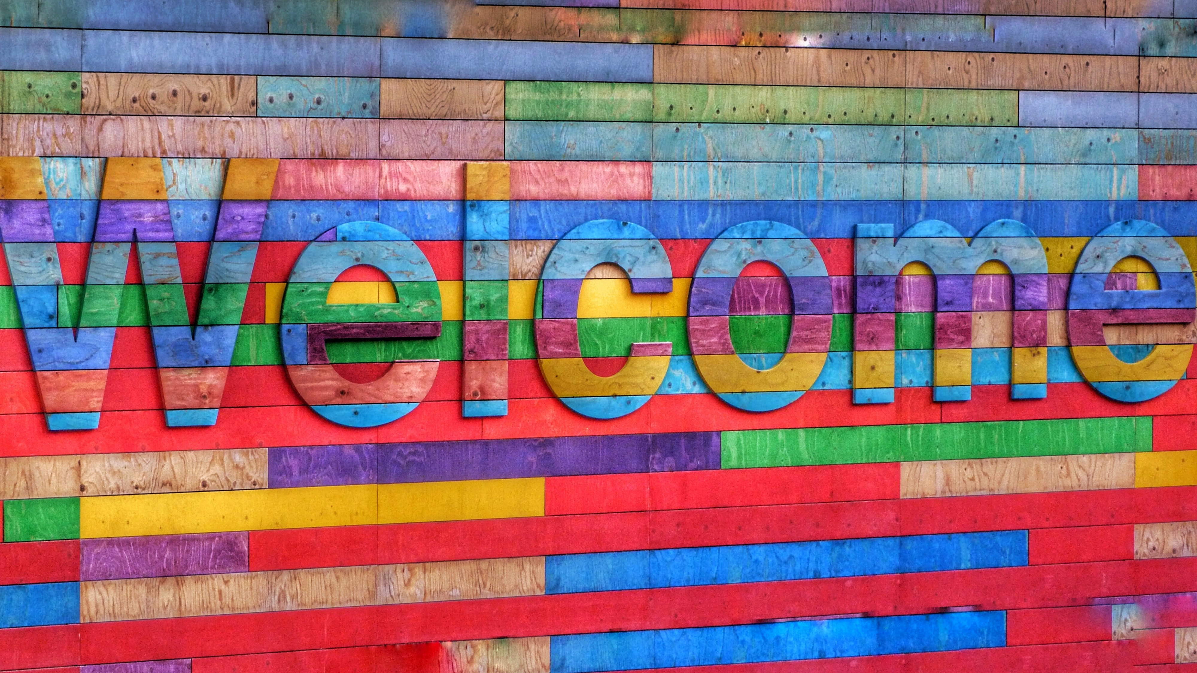"A brightly colored brick wall with the word ""Welcome"" in contrasting bright colors on it."