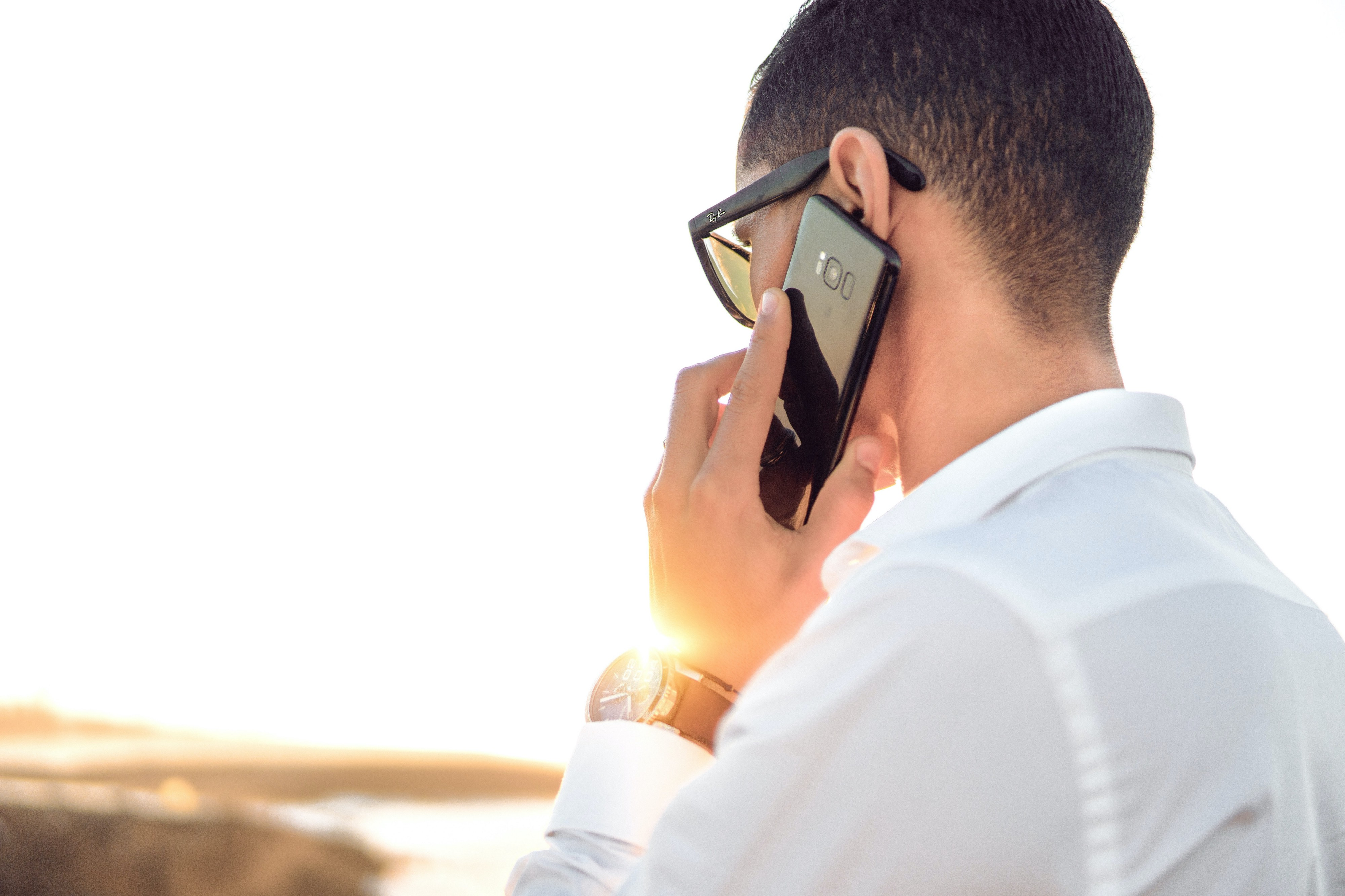 Man with glasses making a phone call