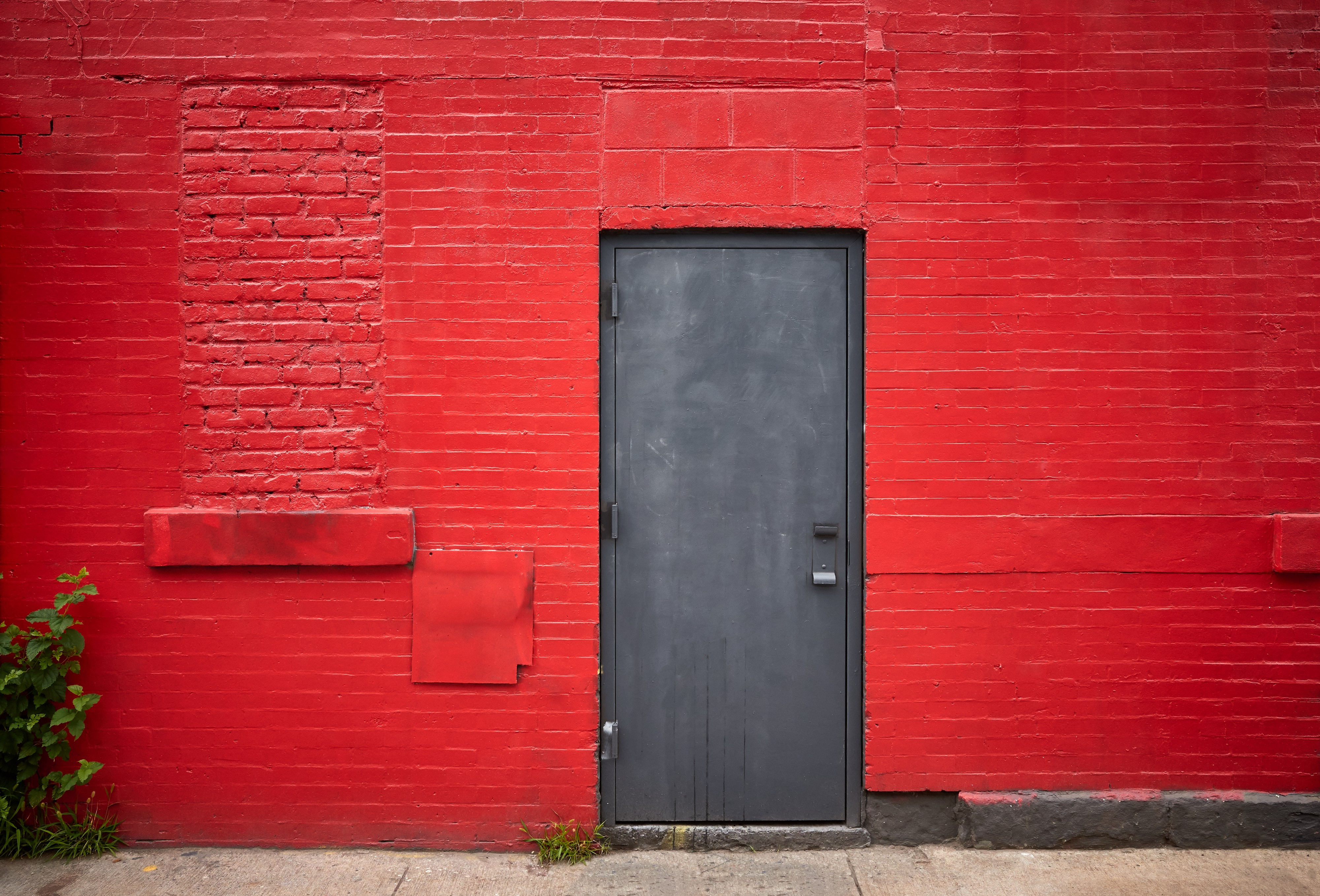 A dark door stands closed in a bright red brick wall.