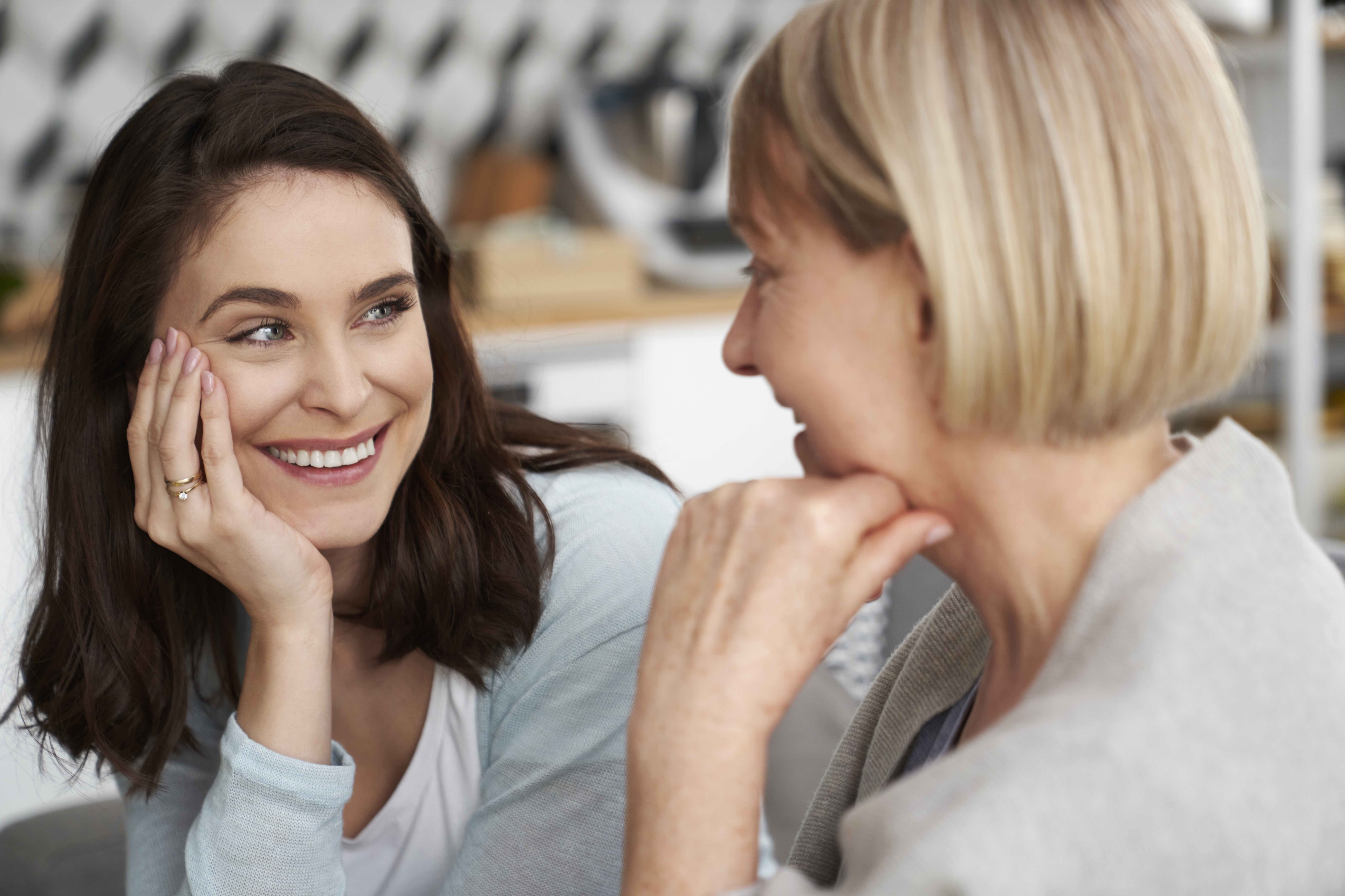Two women of different ages smile and chat together warmly.