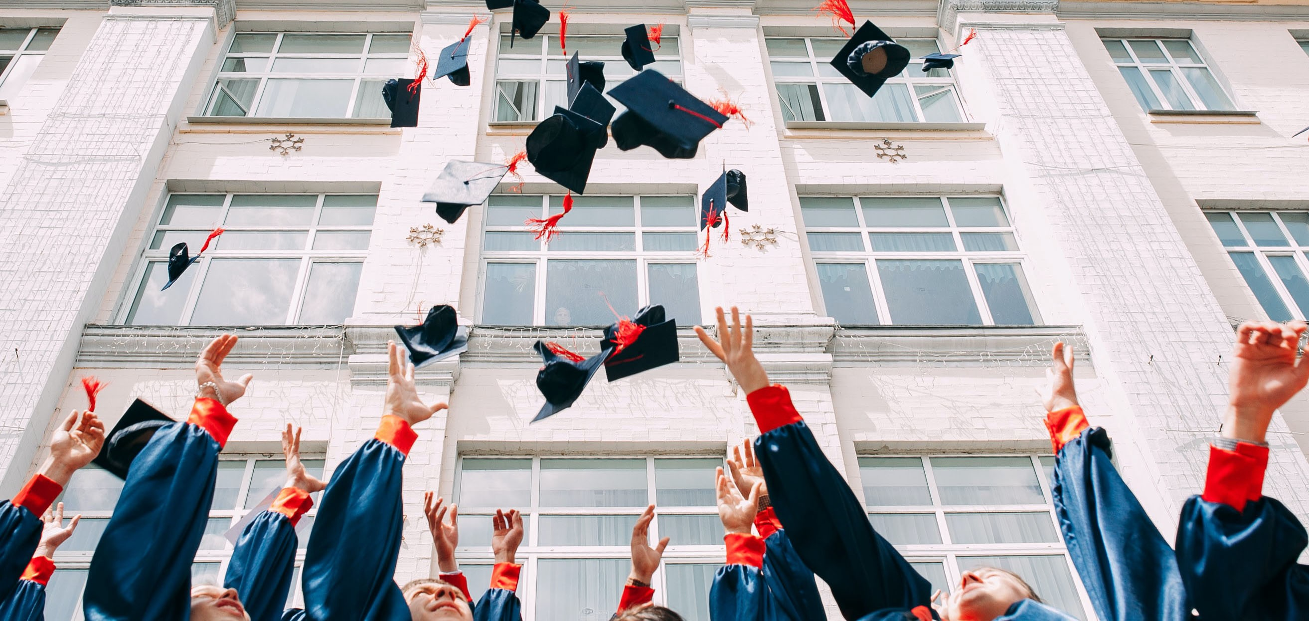 Group of fresh graduates students throwing their academic hats in the air in front of a building.