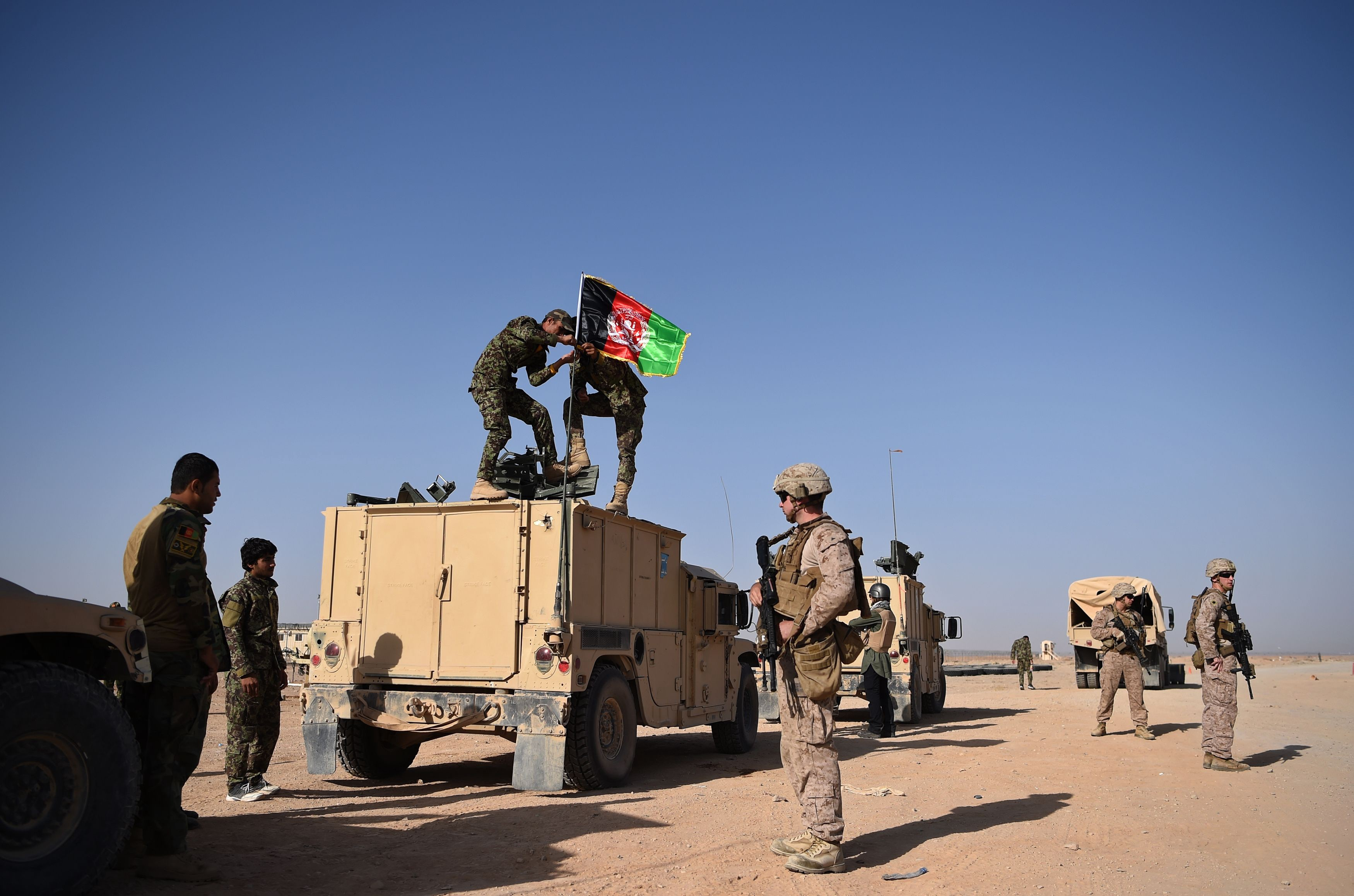 A US Marine looks on as two Afghan National Army soldiers stand in the desert on an armoured vehicle and raise the Afghan National flag.