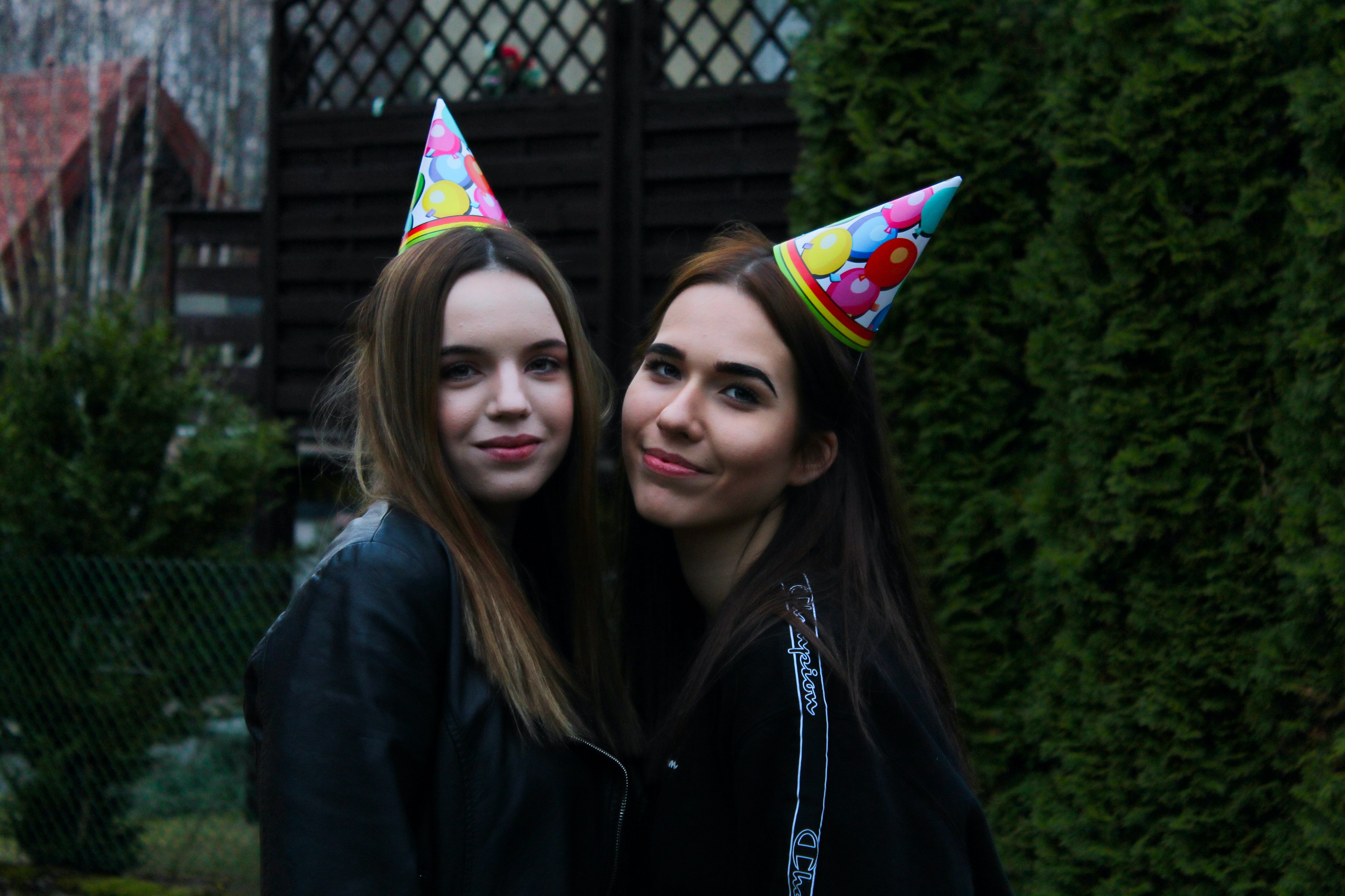 Two young women wearing birthday hats subtly smiling at the camera.