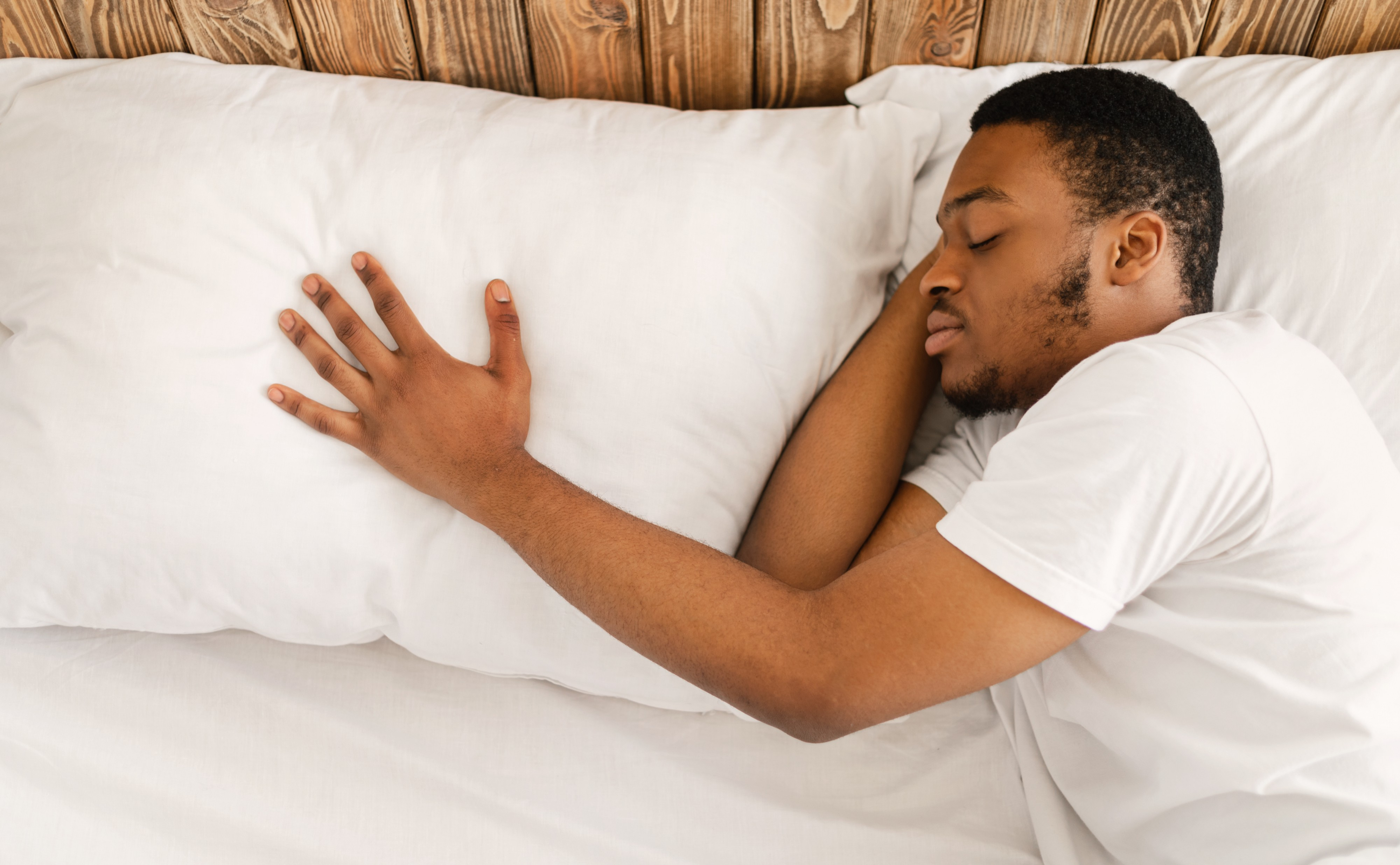 A man sleeps alone and rests his hand on the pillow where his partner used to sleep.