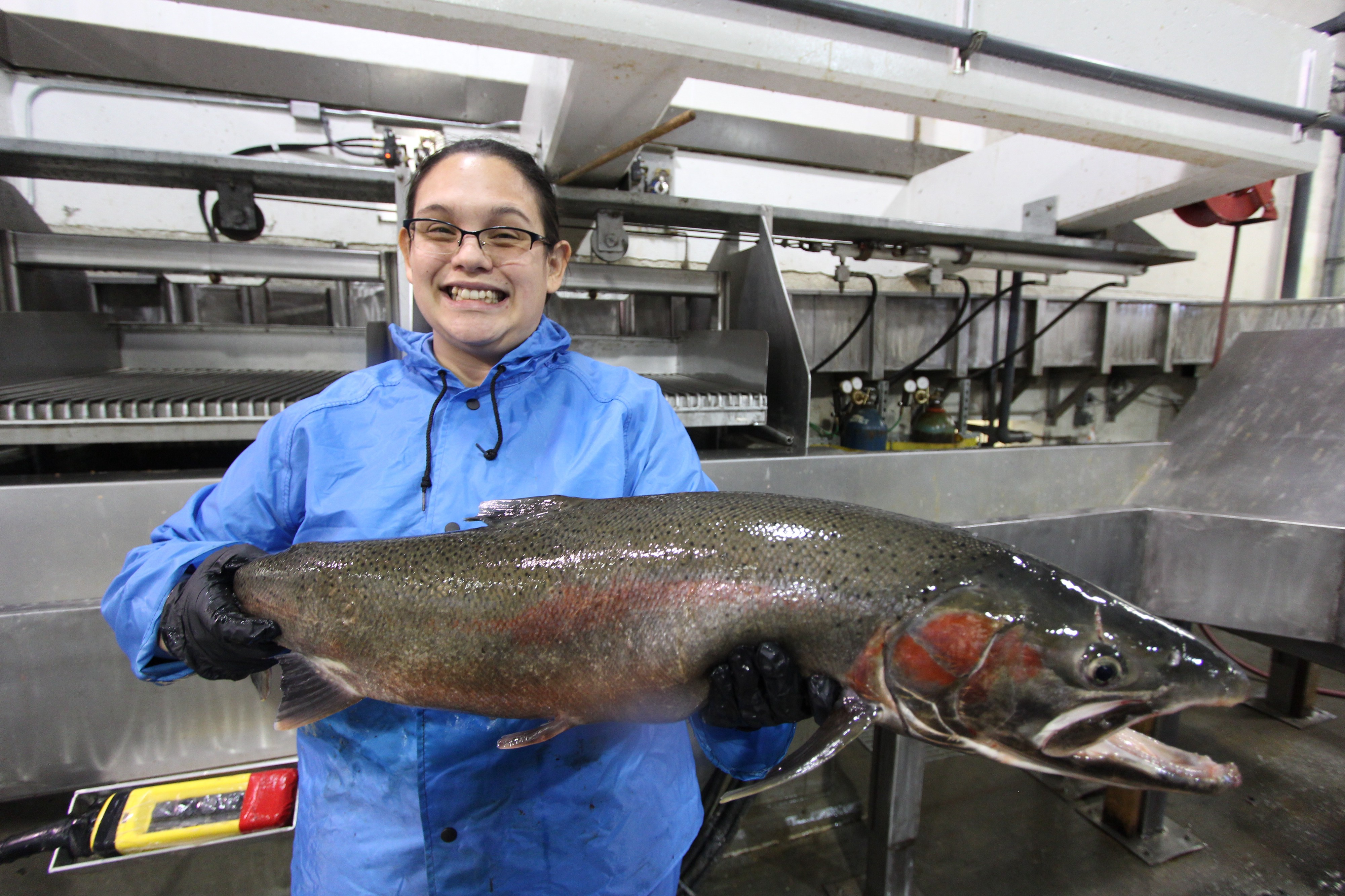 AmeriCorps member Kylee shows off a smile and a huge salmon