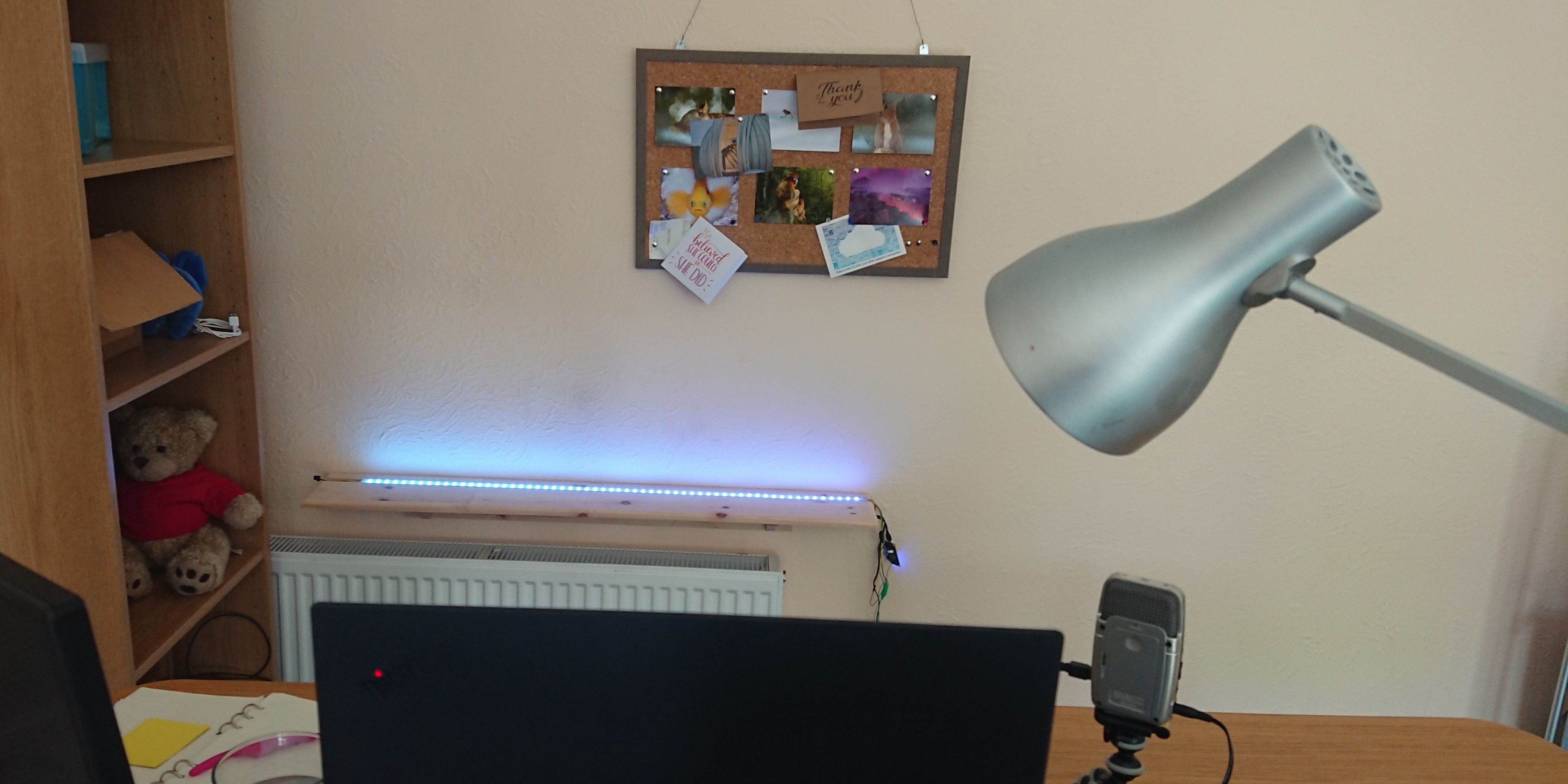 Webcam's eye view, showing top of laptop, pinboard and shelf behind desk