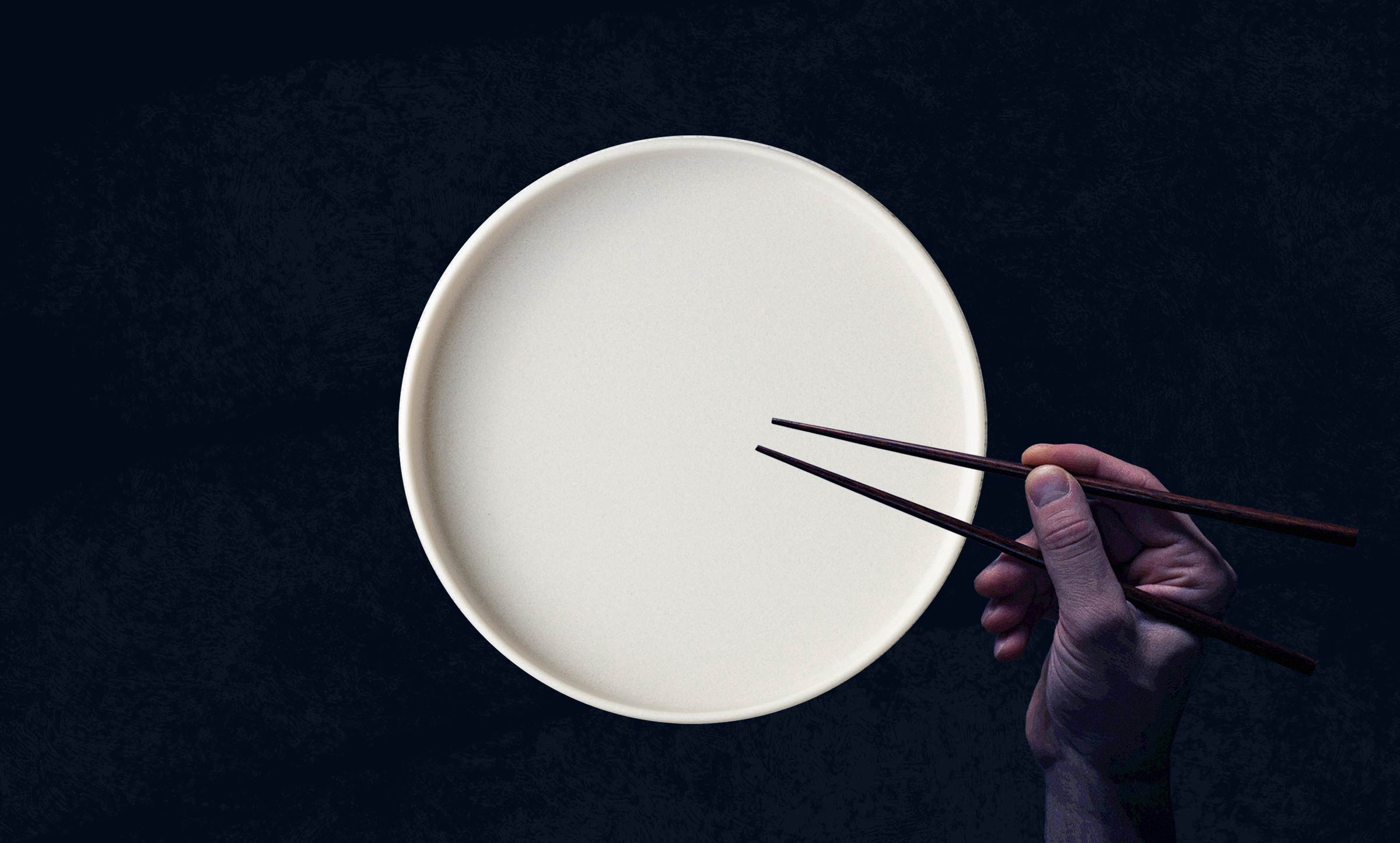 A white, empty plate with a waiting hand holding chopsticks.