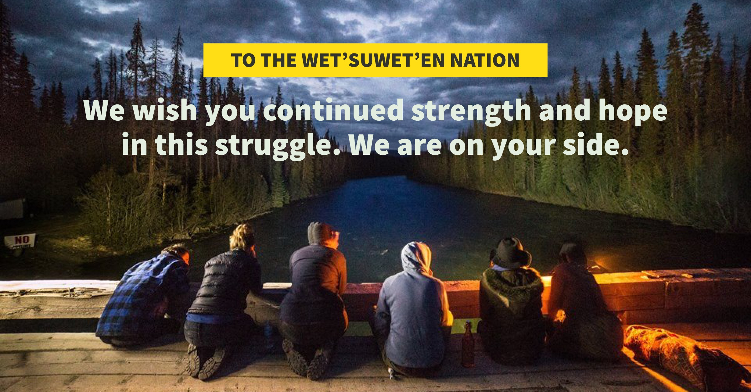 People sitting on a bridge overlooking a river with statement of support overlayed