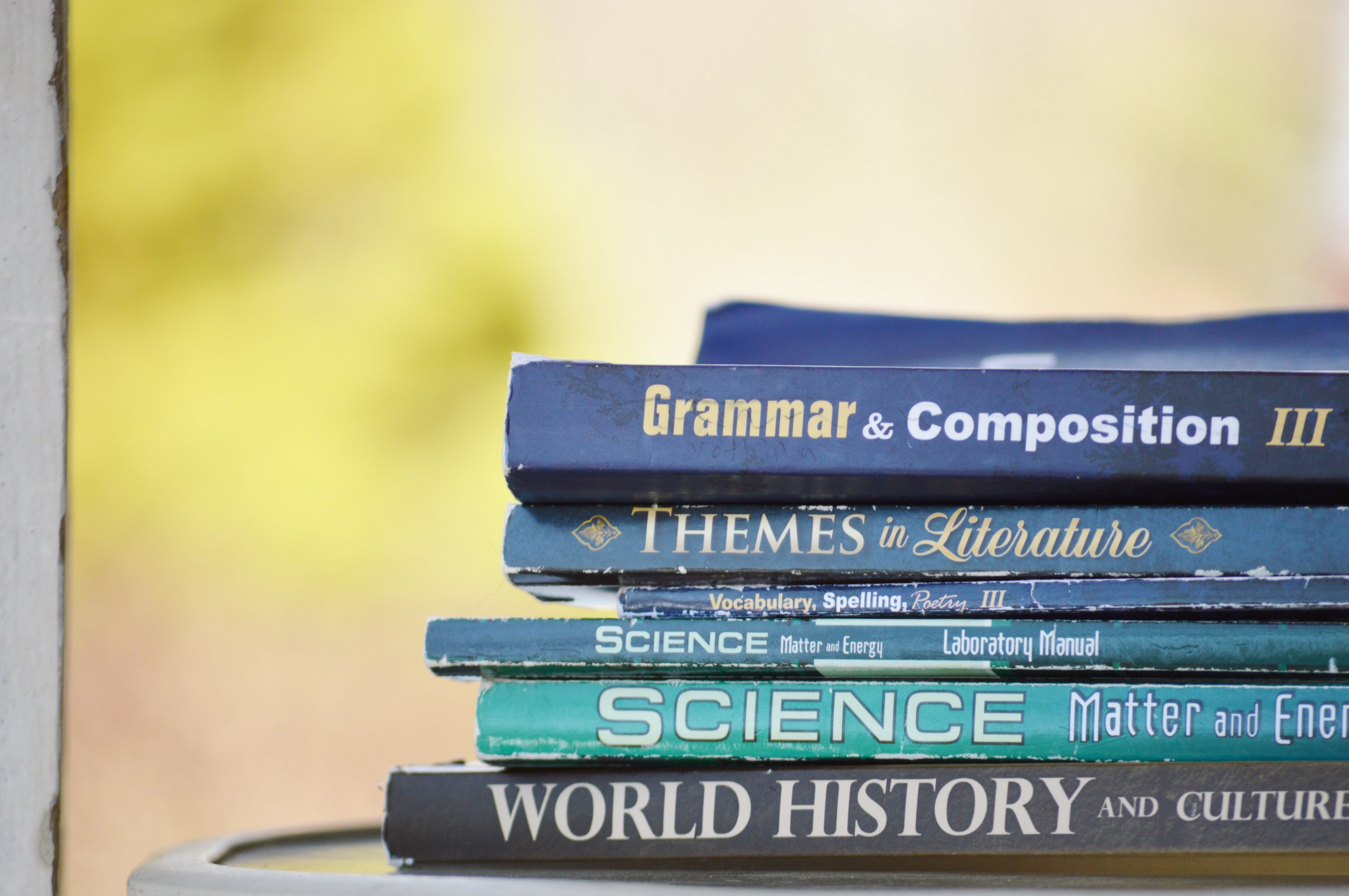 A set of old text books on a table, tattered and worn