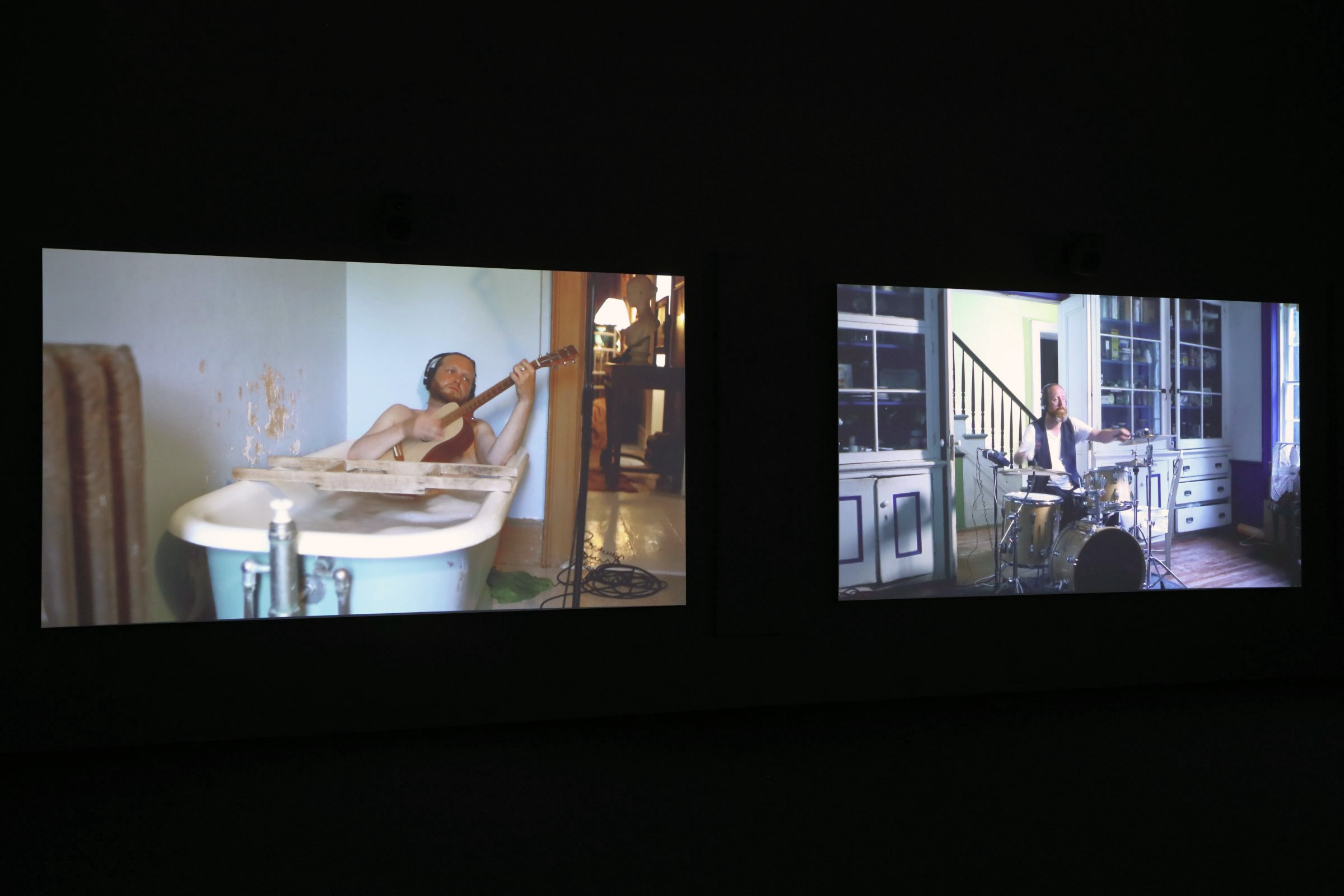 Installation view of two screens on a black background featuring musicians playing alone in separate rooms.