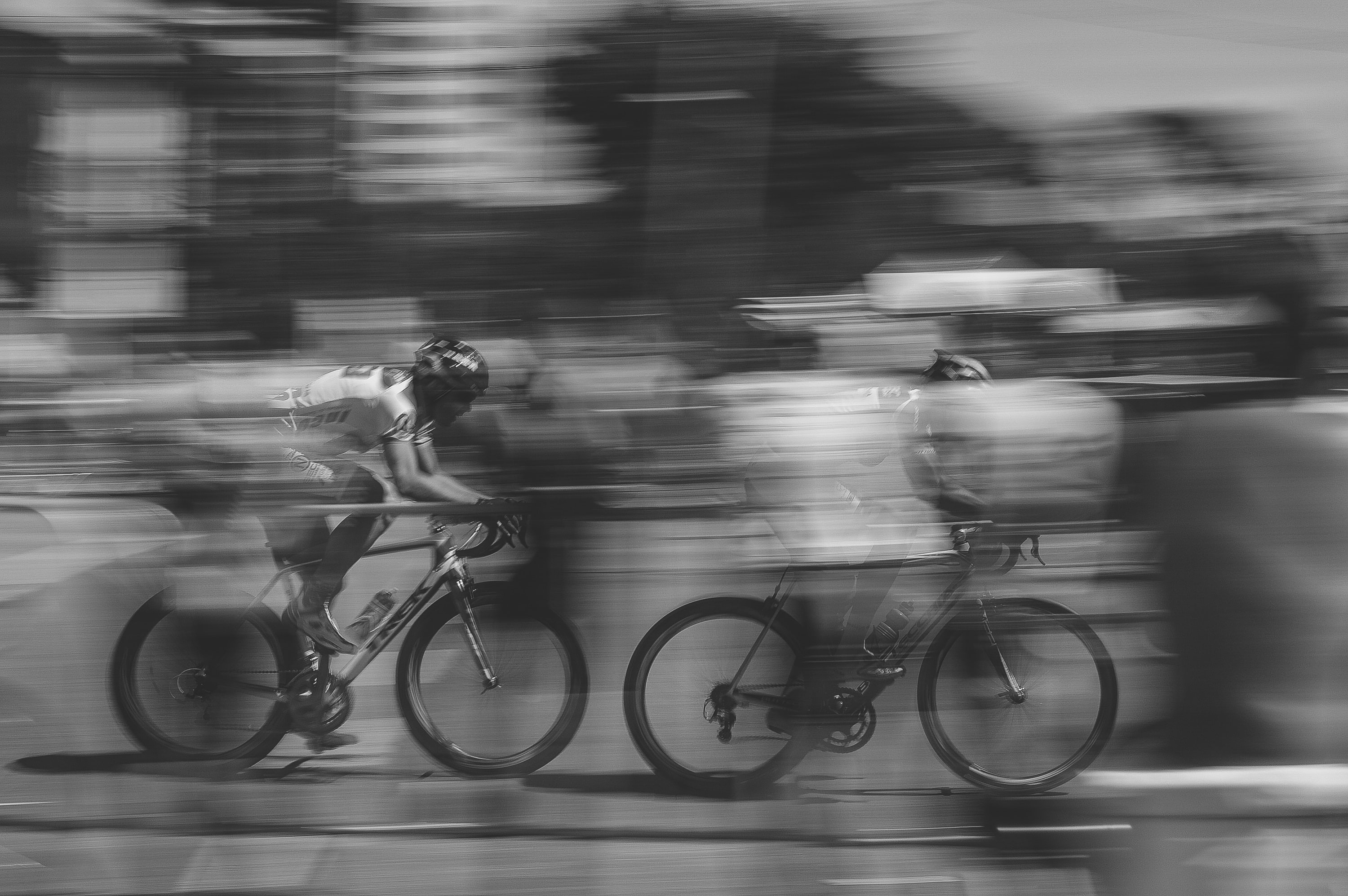 A black and white photo with blur of movement showing speed, racing, fast past. pursuit. Momentum.