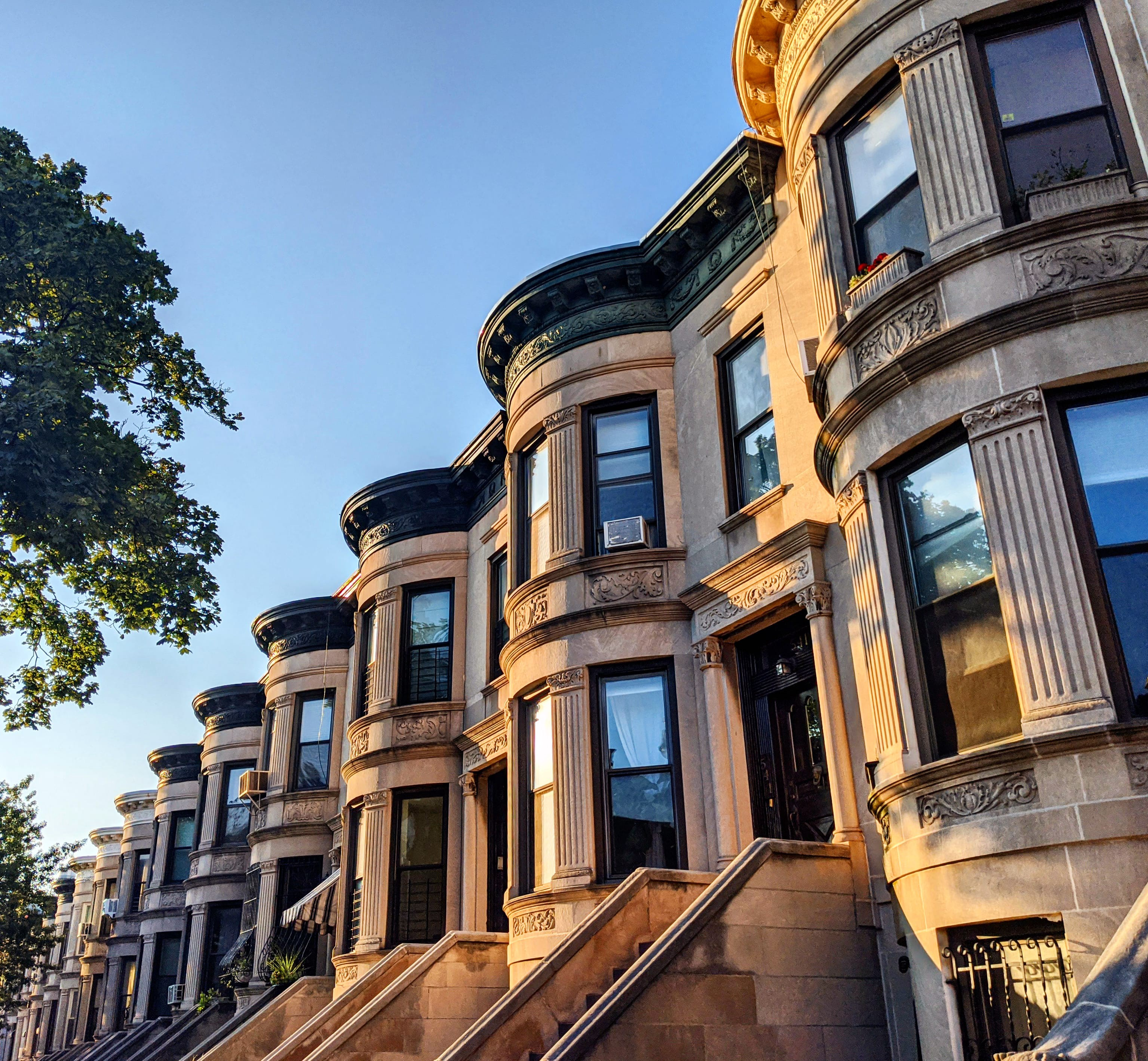 A block of brownstone apartments in Brooklyn as the sun sets