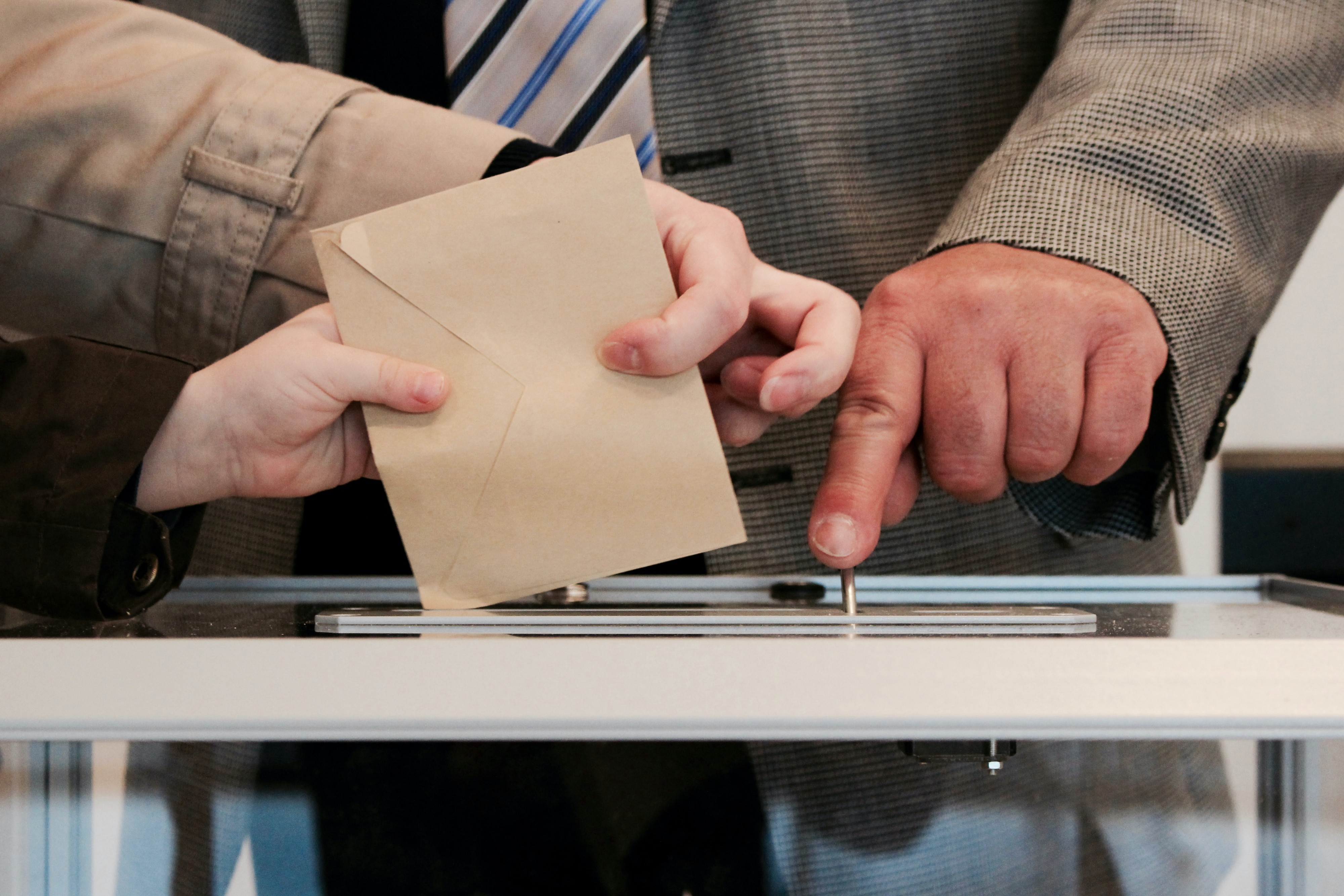 Multiple people's hands guide an envelope into a ballot box