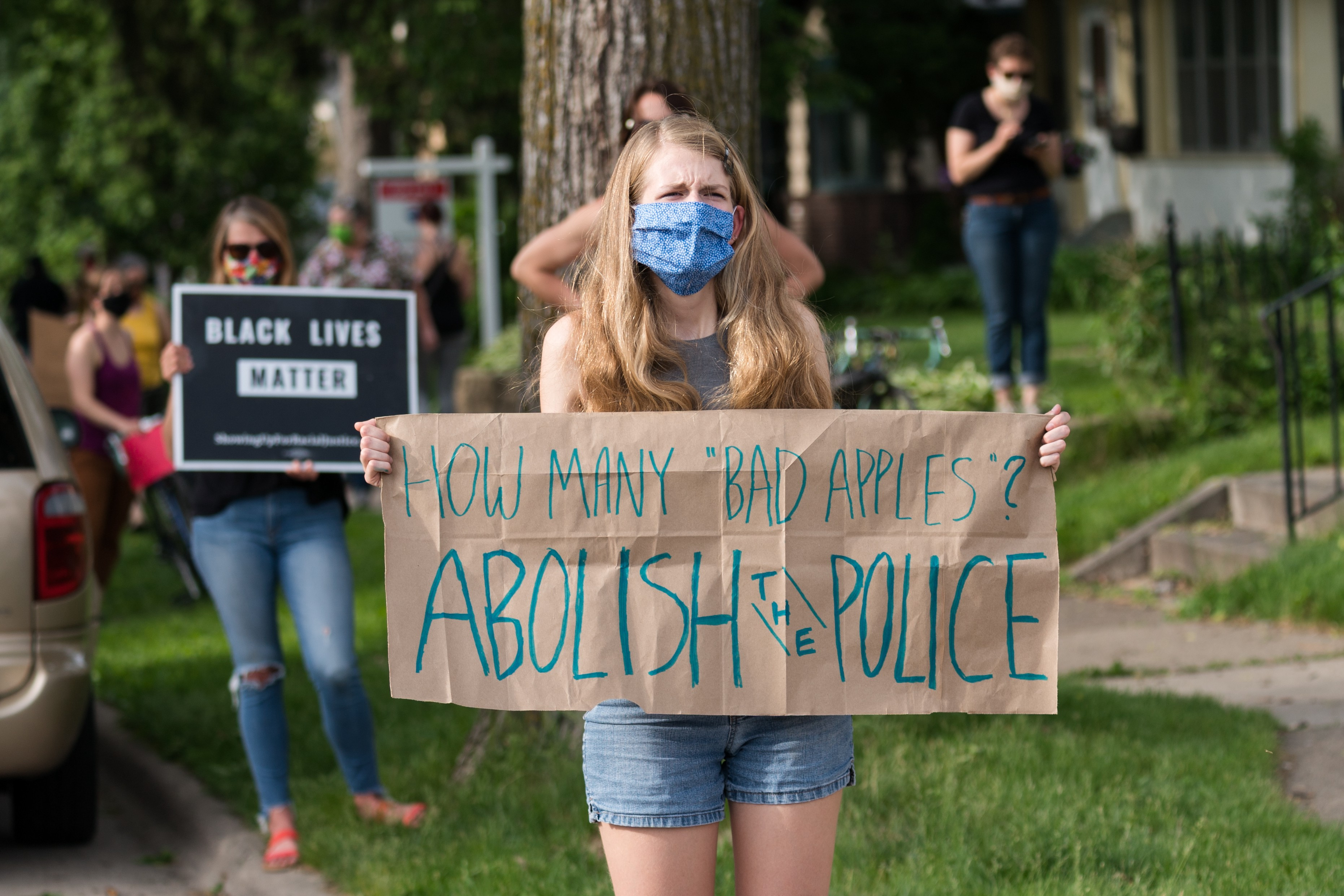 "How Many ""Bad Apples""? Abolish the Police sign held by Minneapolis protester after the death of George Floyd."
