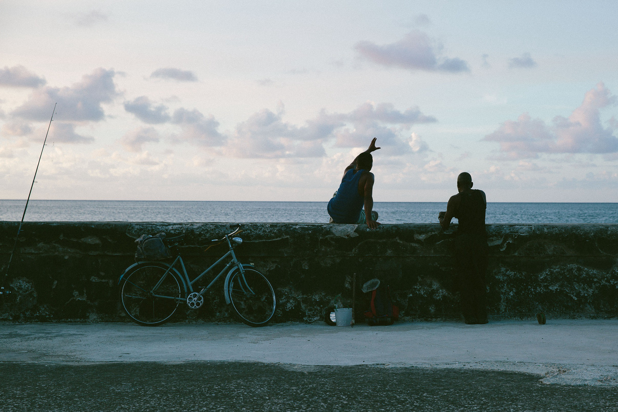 Two people sitting on a wall looking out to the ocean.