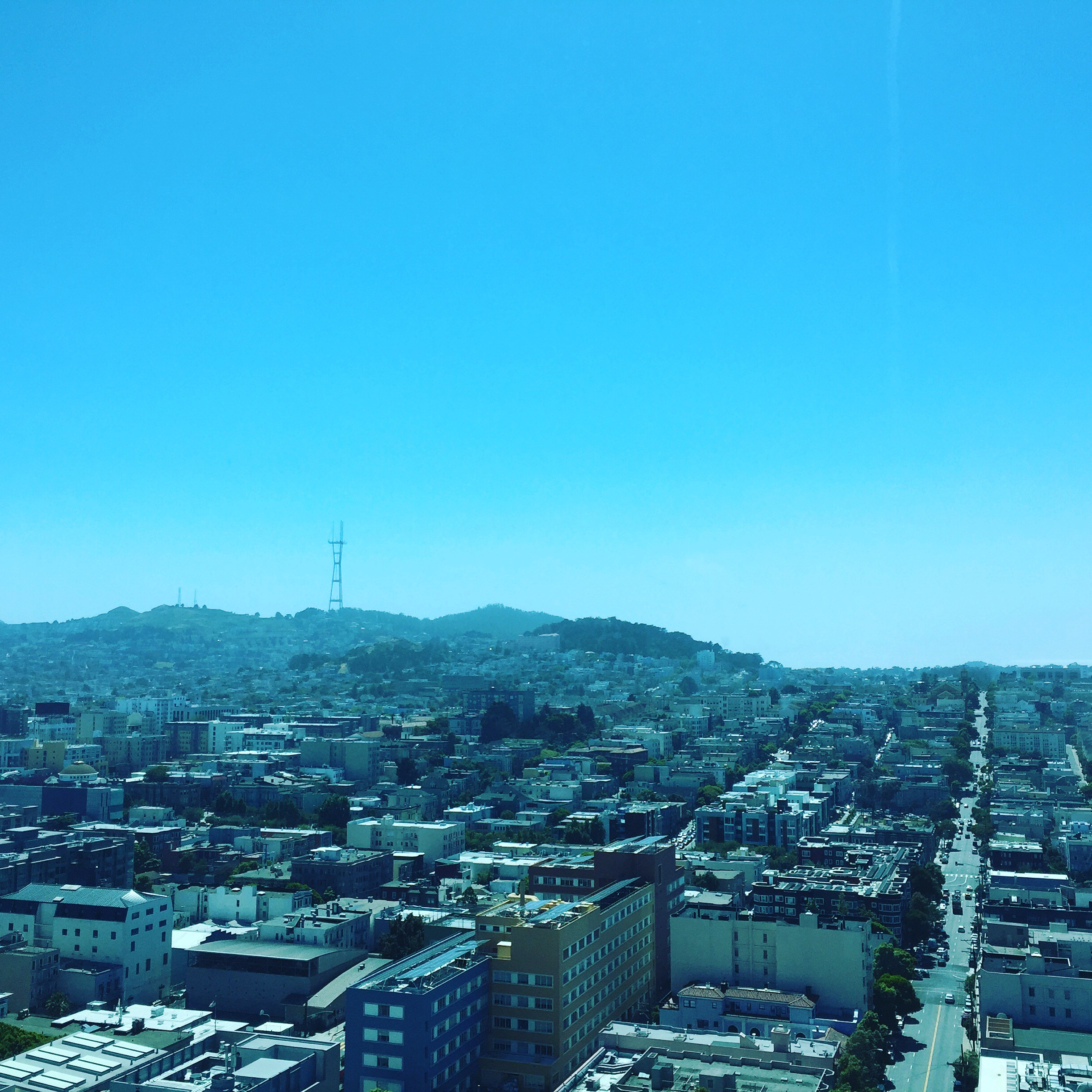 Densely clustered homes with a hillside in the background. Sutro Tower is at the top of the hill in the background.