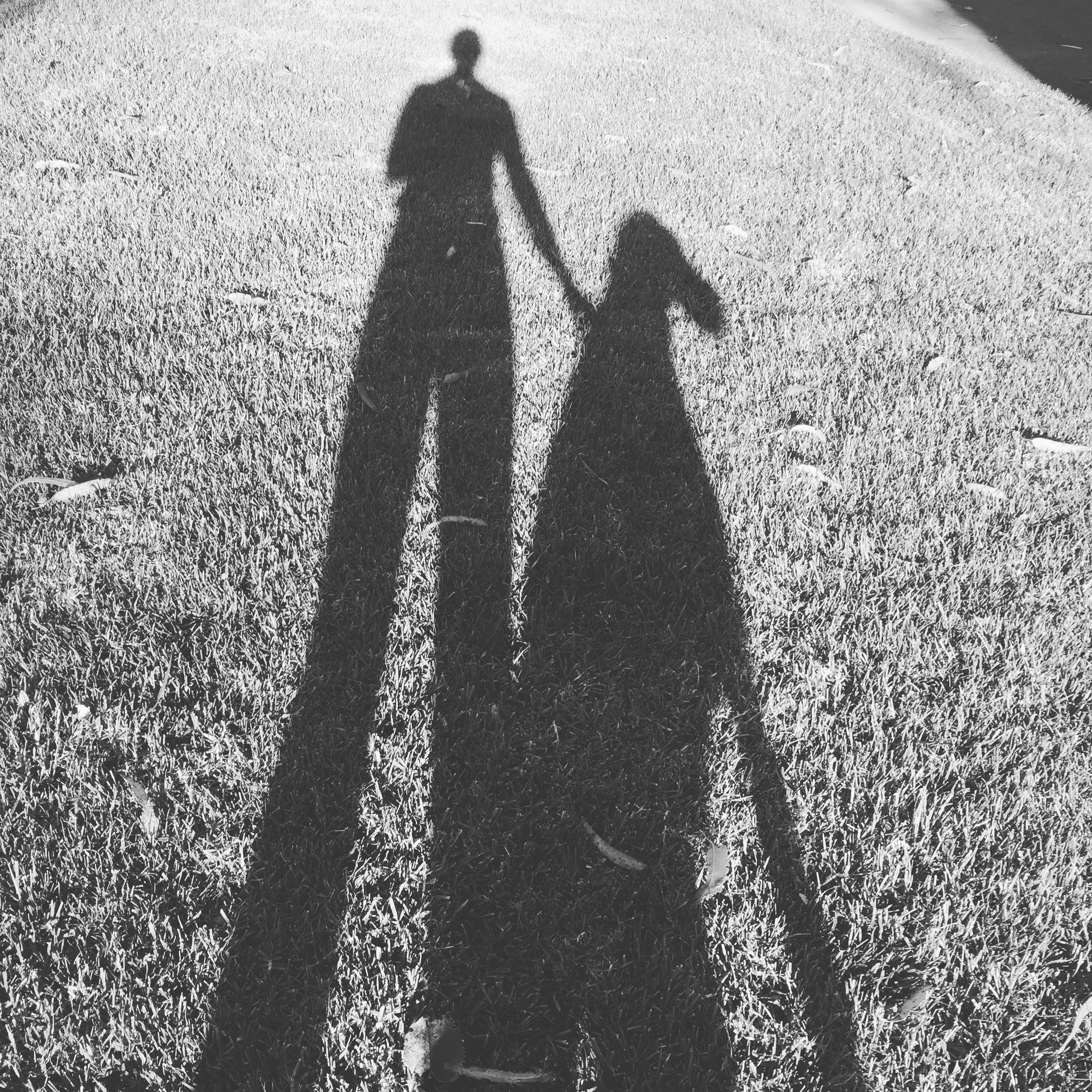 A black and white photo of the author's shadow along with her dog's shadow.
