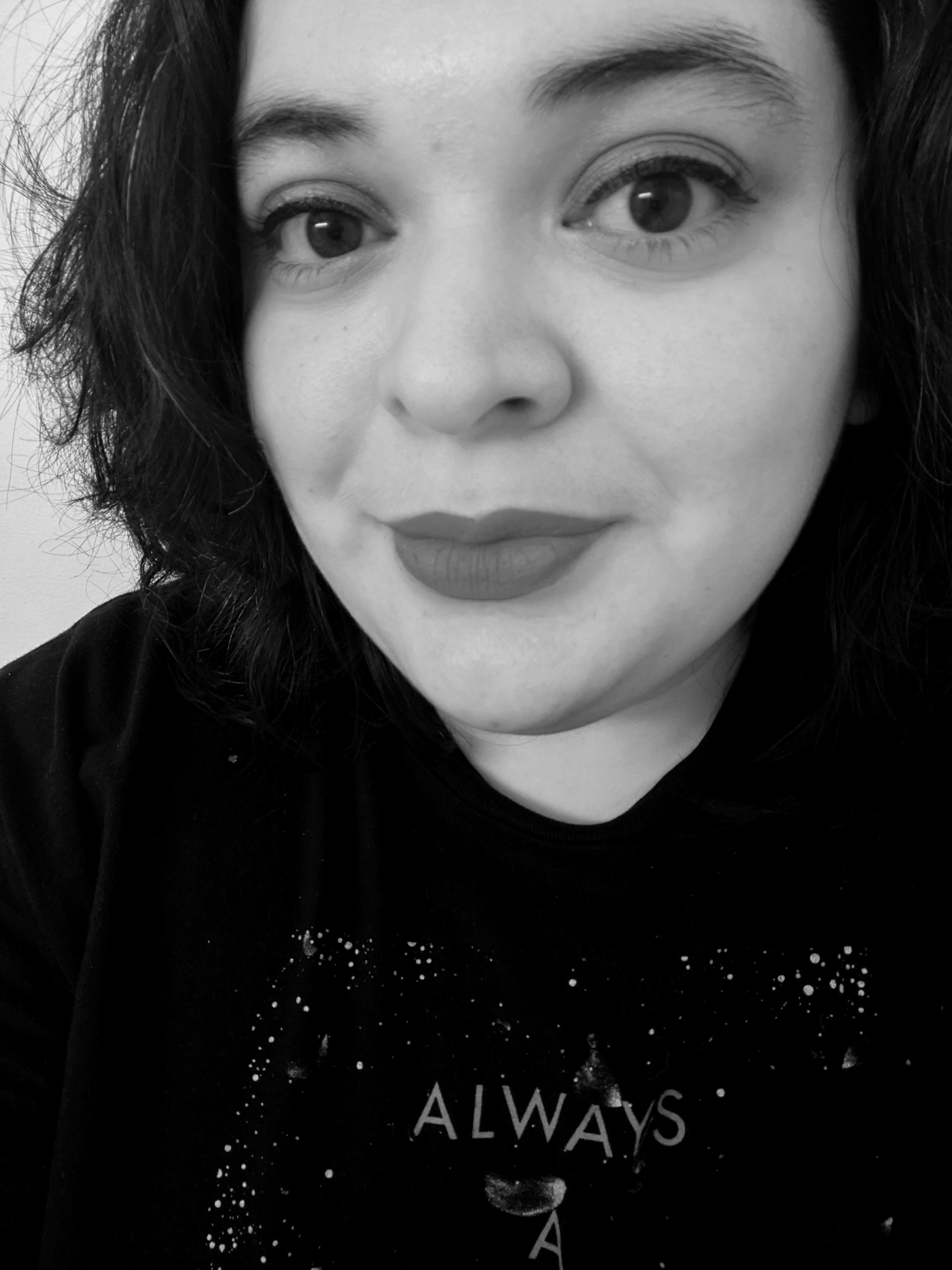 A black-and-white photo of the author. She has short black hair, dark eyes, and very distinct lipstick and wears a black T-shirt.