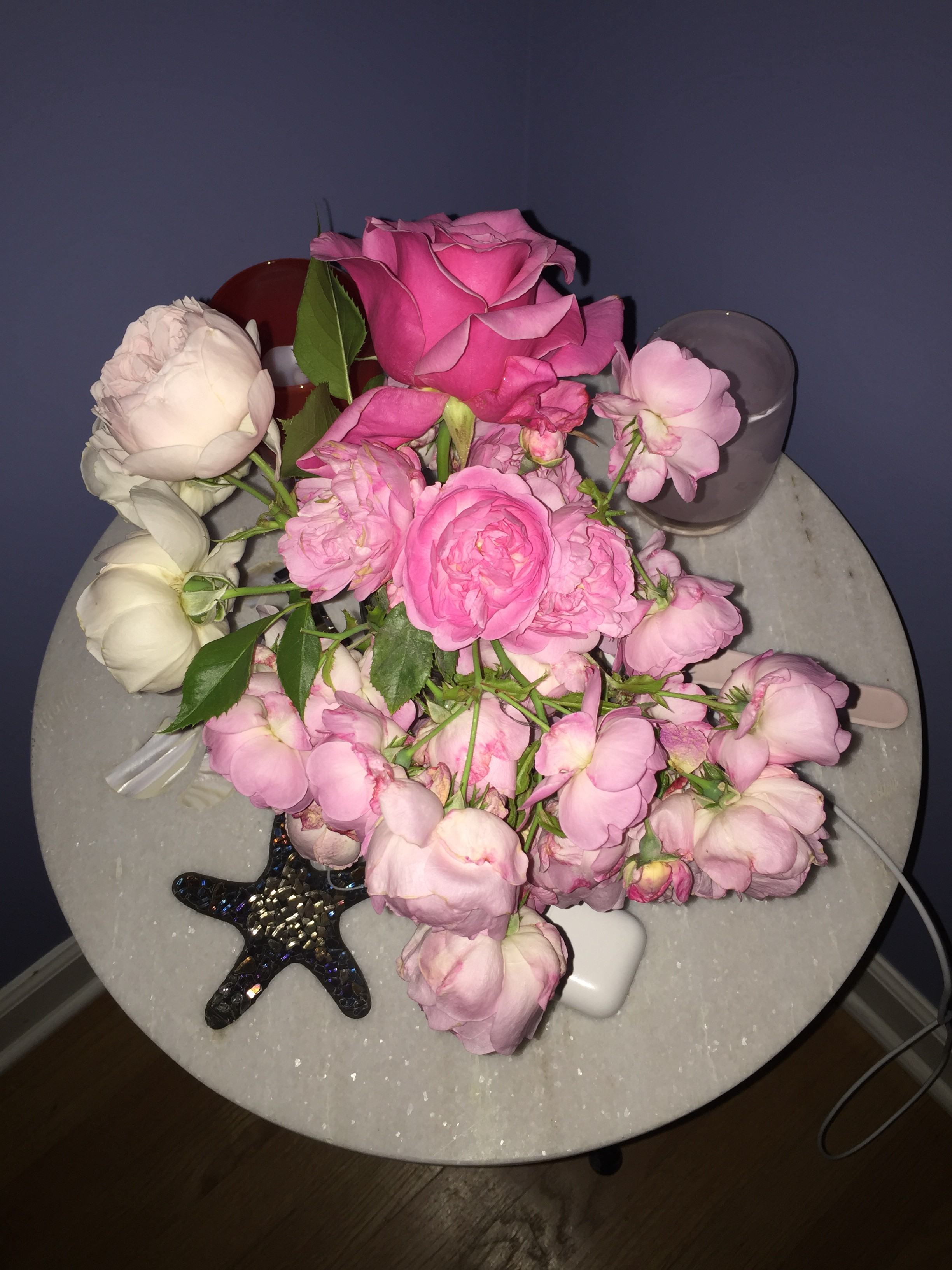 A bouquet of pink roses on a small round table.