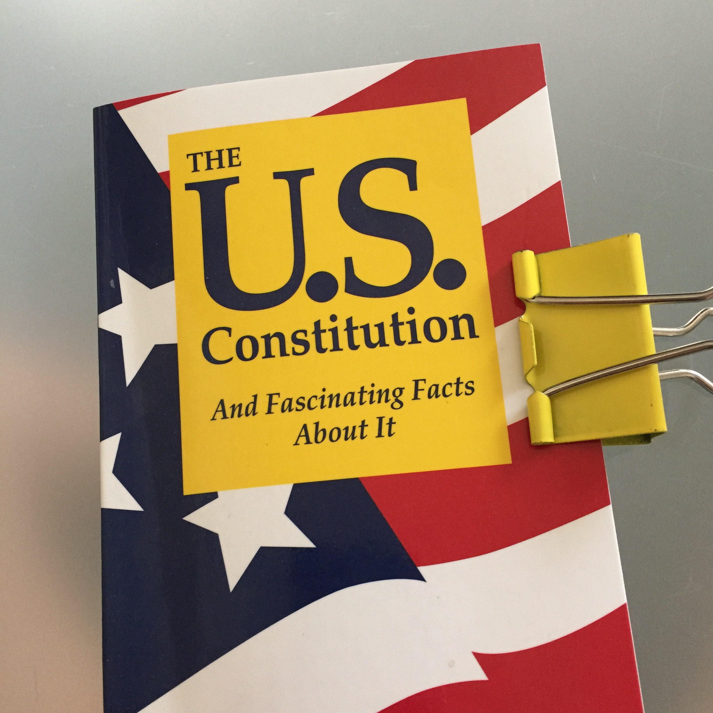 Book cover: U.S. flag background w big yellow block: The U.S. Constitution/And Fascinating Facts About It. Yellow binder clip