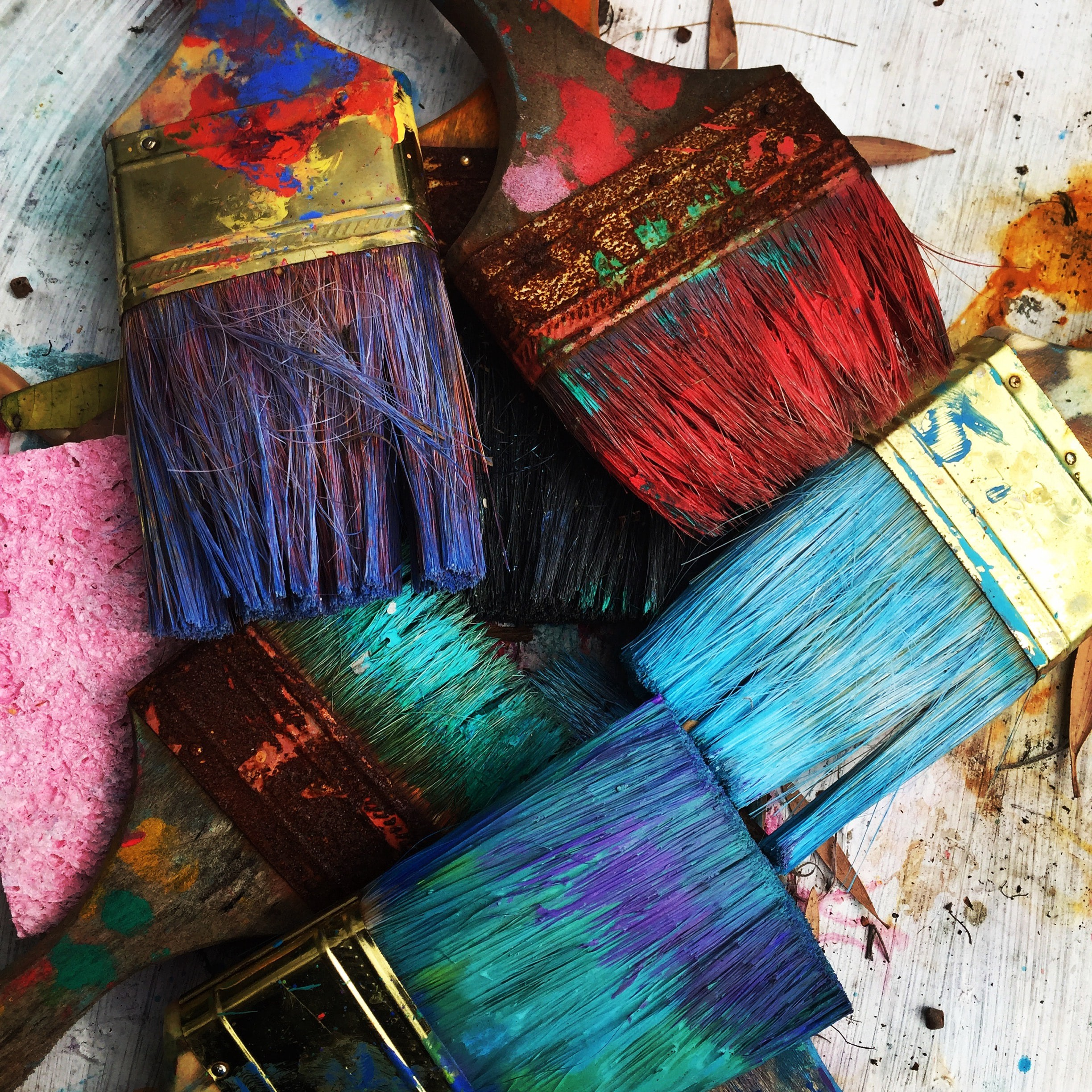 Paintbrushes covered in colorful paint in an artistic array