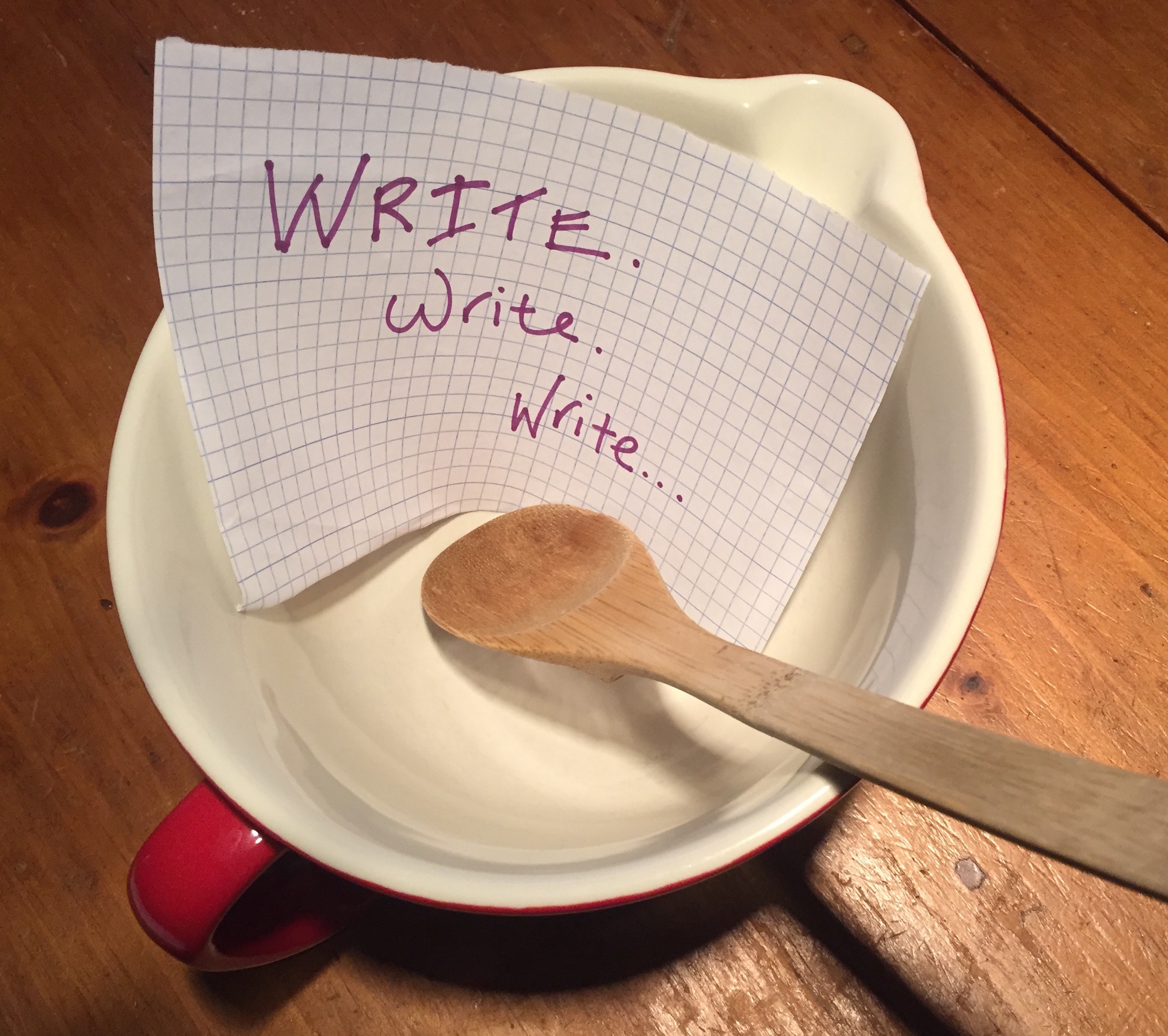 """Mixing bowl and wooden spoon with a piece of paper inside that says """"Write. Write. Write."""""""