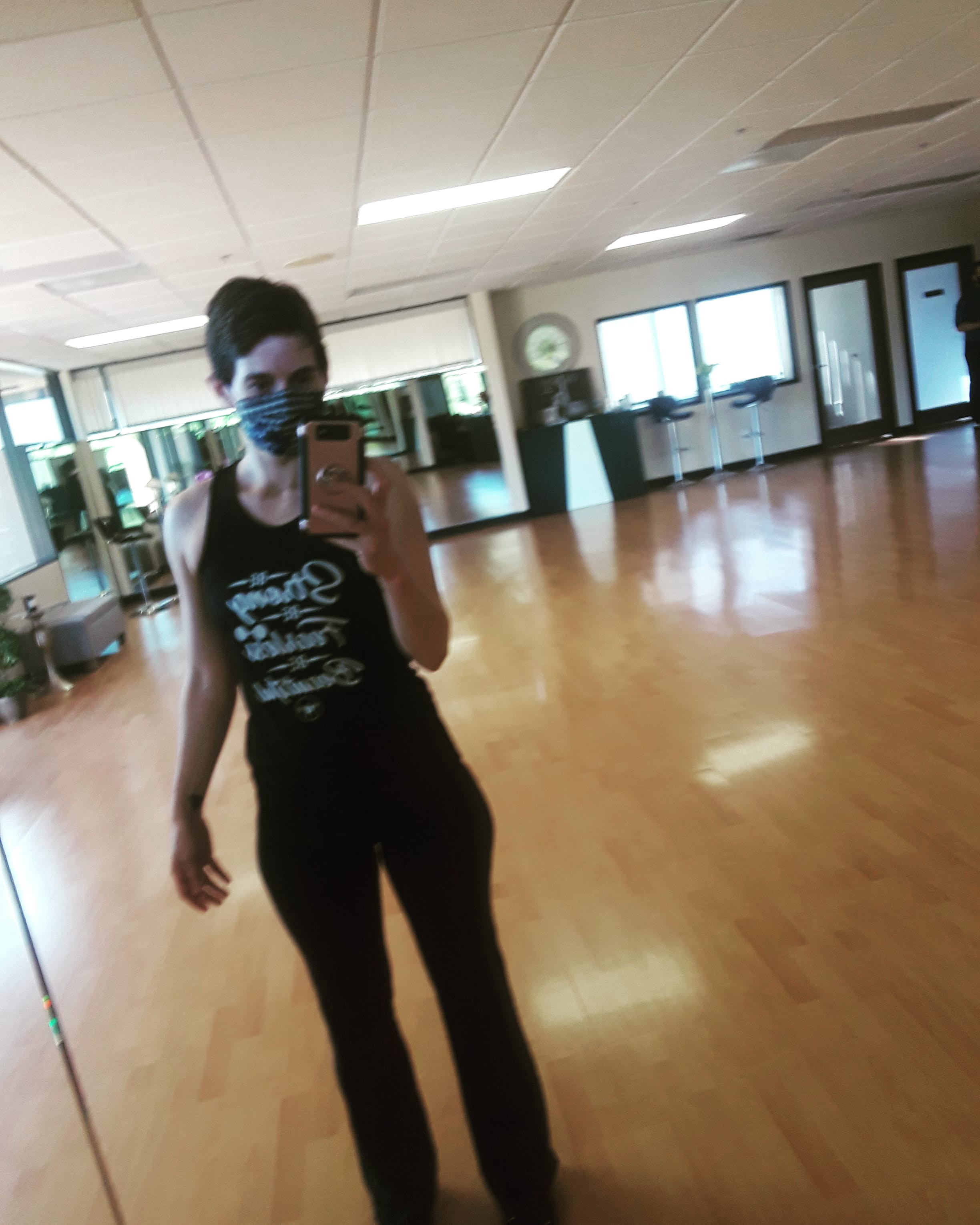 Woman wearing a face mask, taking a selfie in the mirror at an empty dance studio.