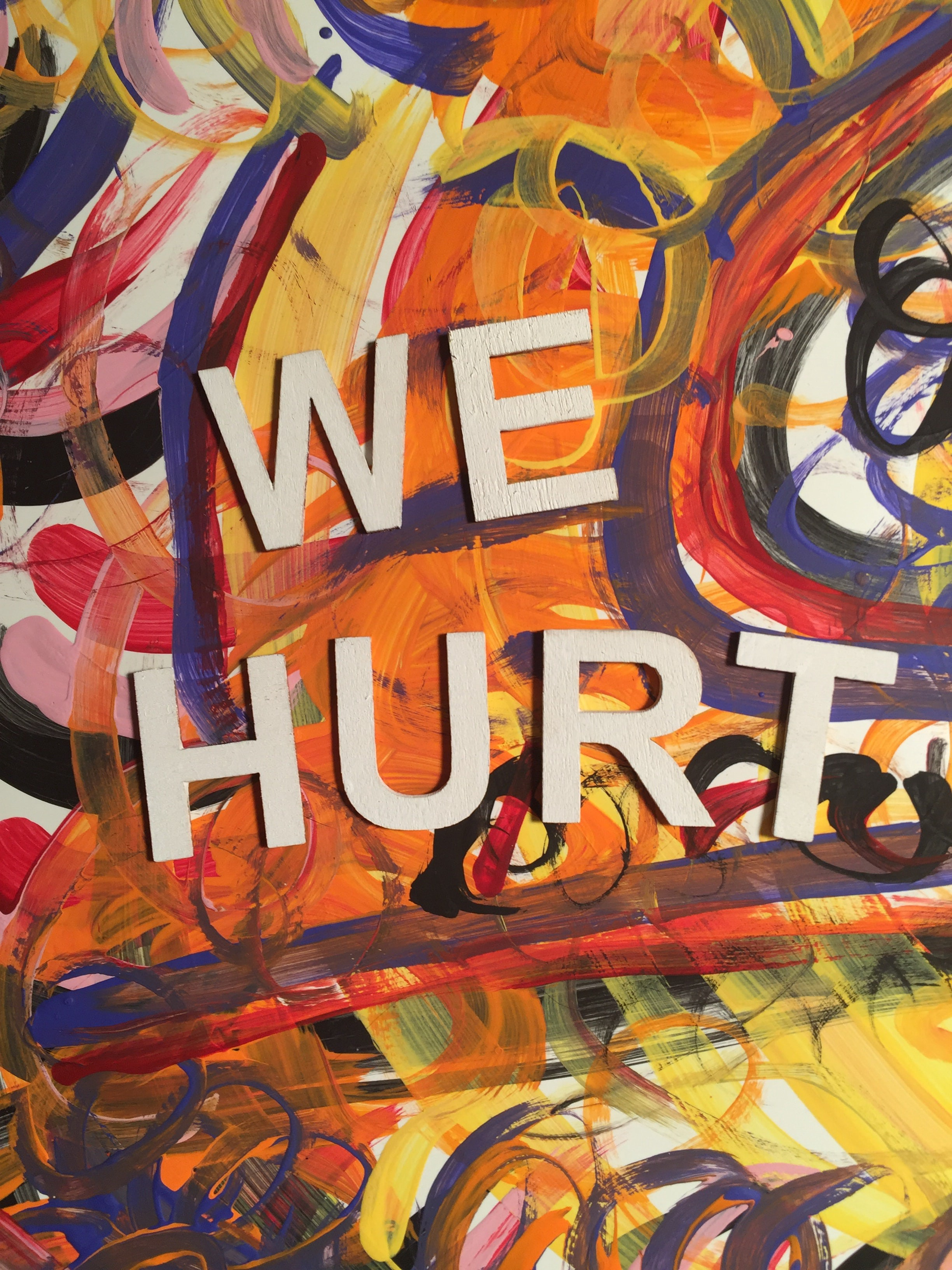 """Colorful abstract painting with the words """"We hurt"""" is big white and black letters."""