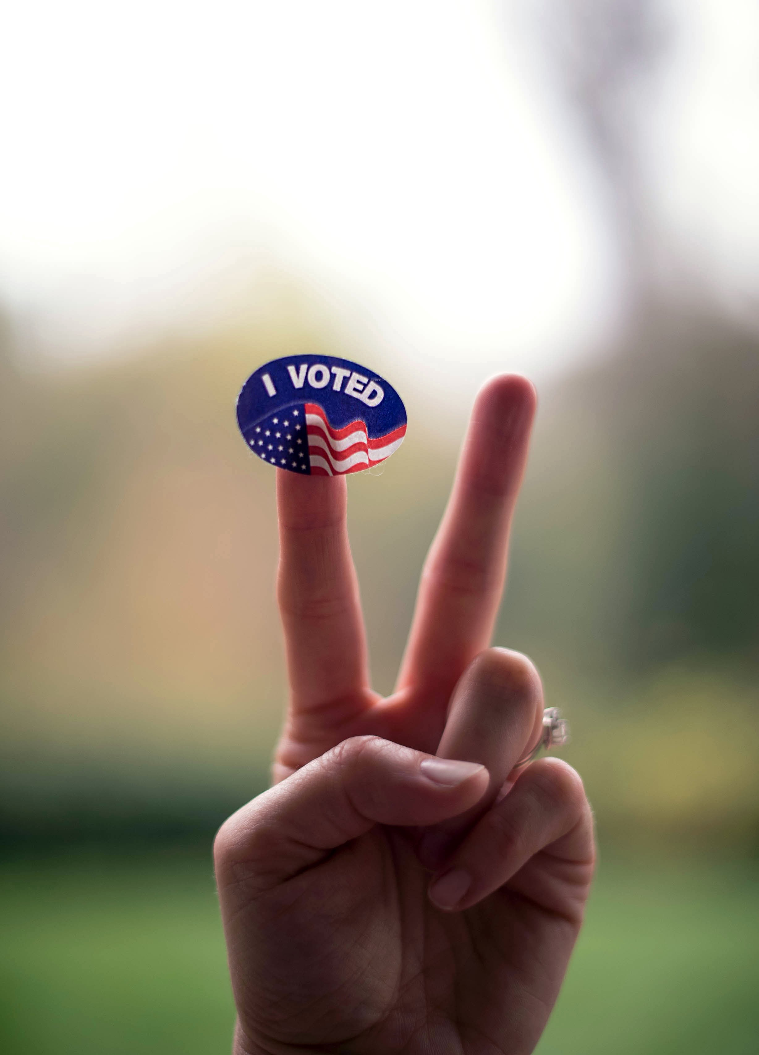 """Two fingers in the air with an """"I Voted"""" sticker on the left finger"""