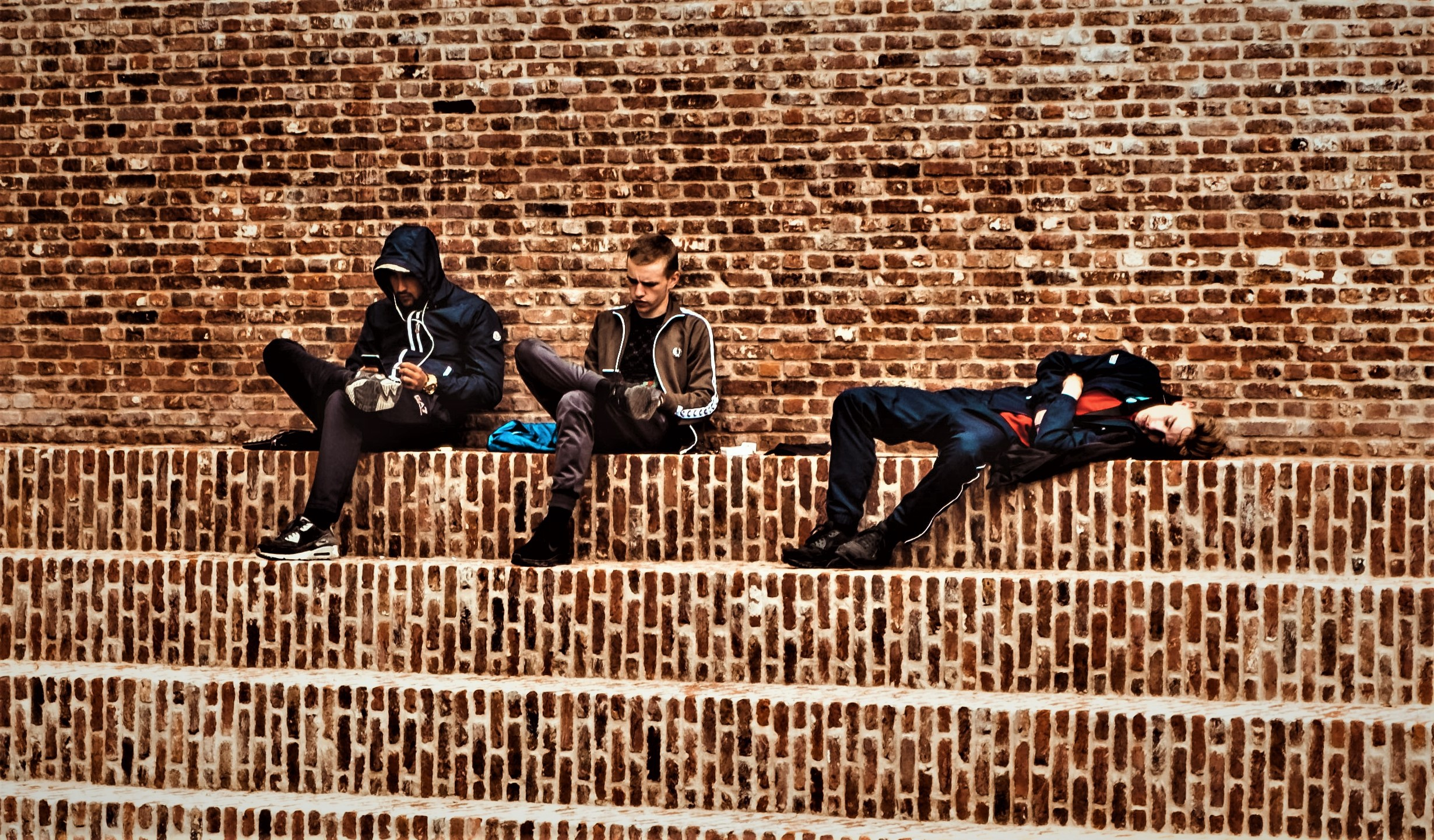 three young men sitting on steps looking at cell phones and sleeping