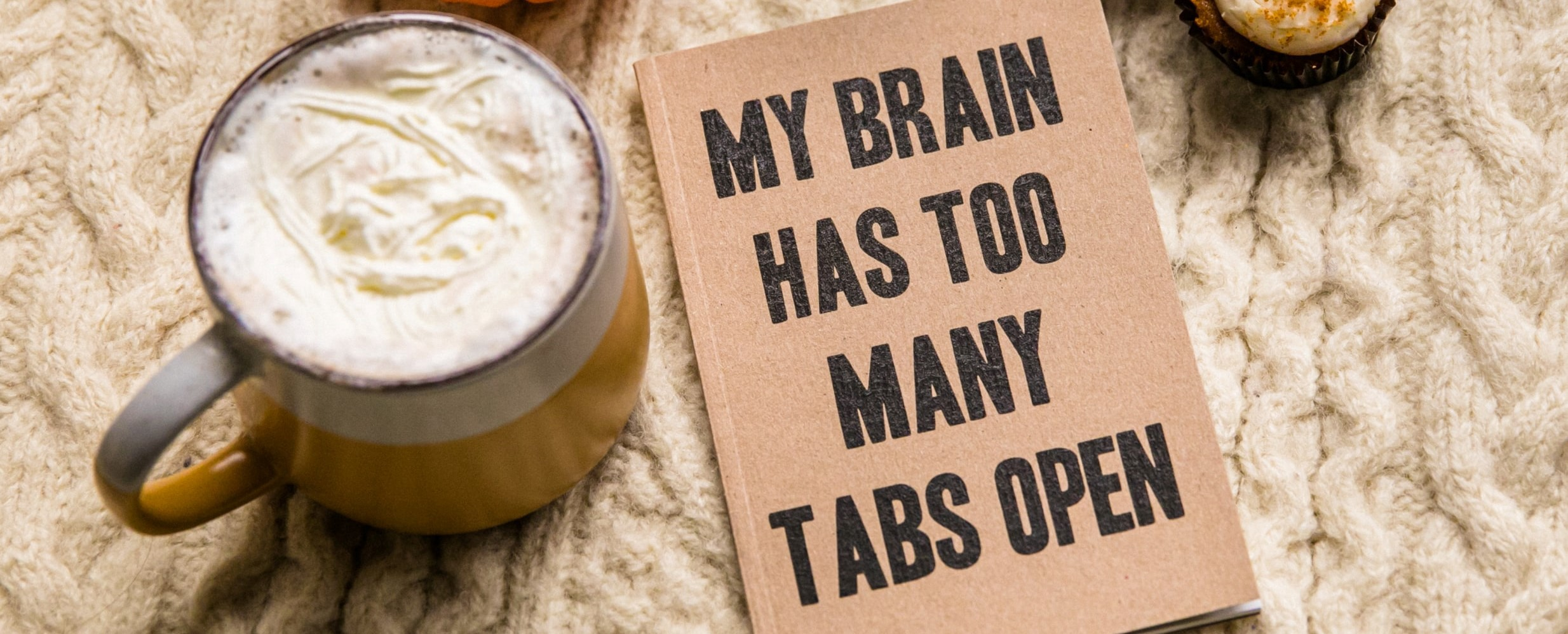 "A brown notepad with the words ""My brain has too many tabs open"". To the left is a mug of a drink with cream on the top. They are sitting on a cream chunky knit surface."