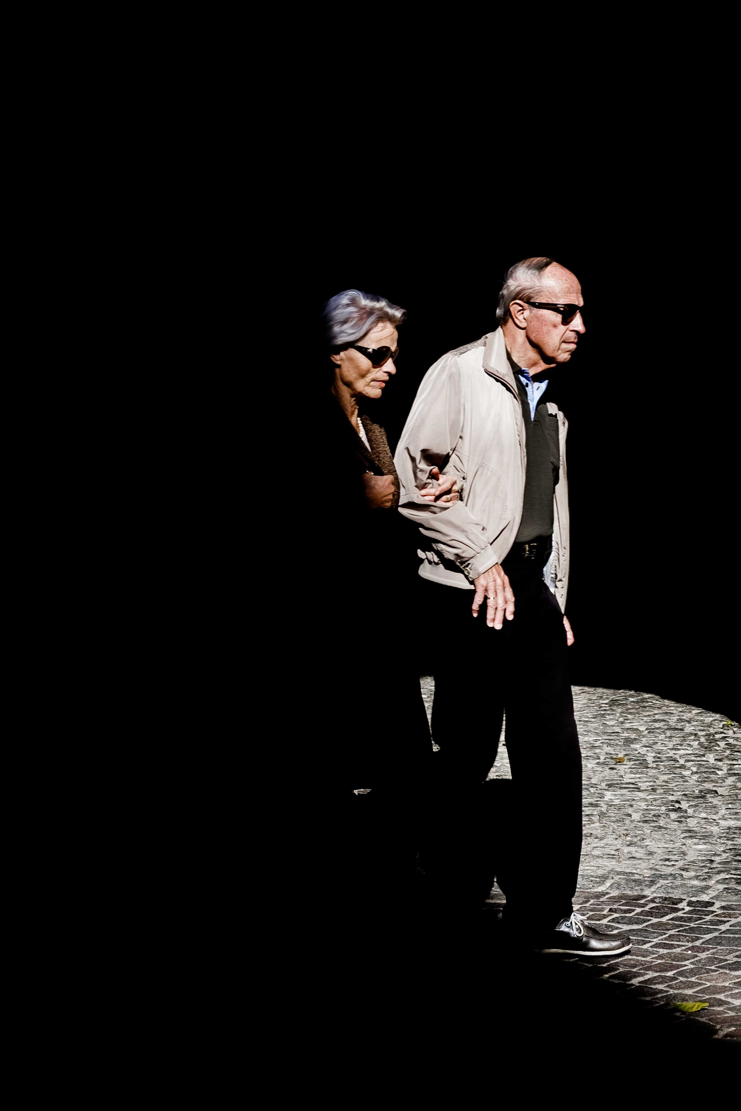 Man and woman linking arms and wearing sunglasses walking down the street