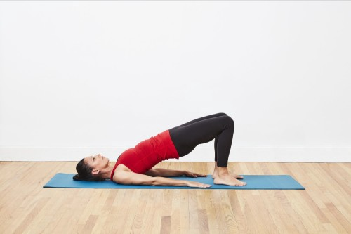 A side-view of a woman doing a glute bridge