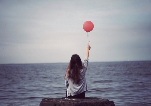 A girl sitting on a rock facing the ocean (opposite to the camera) and just about to let go of a balloon.