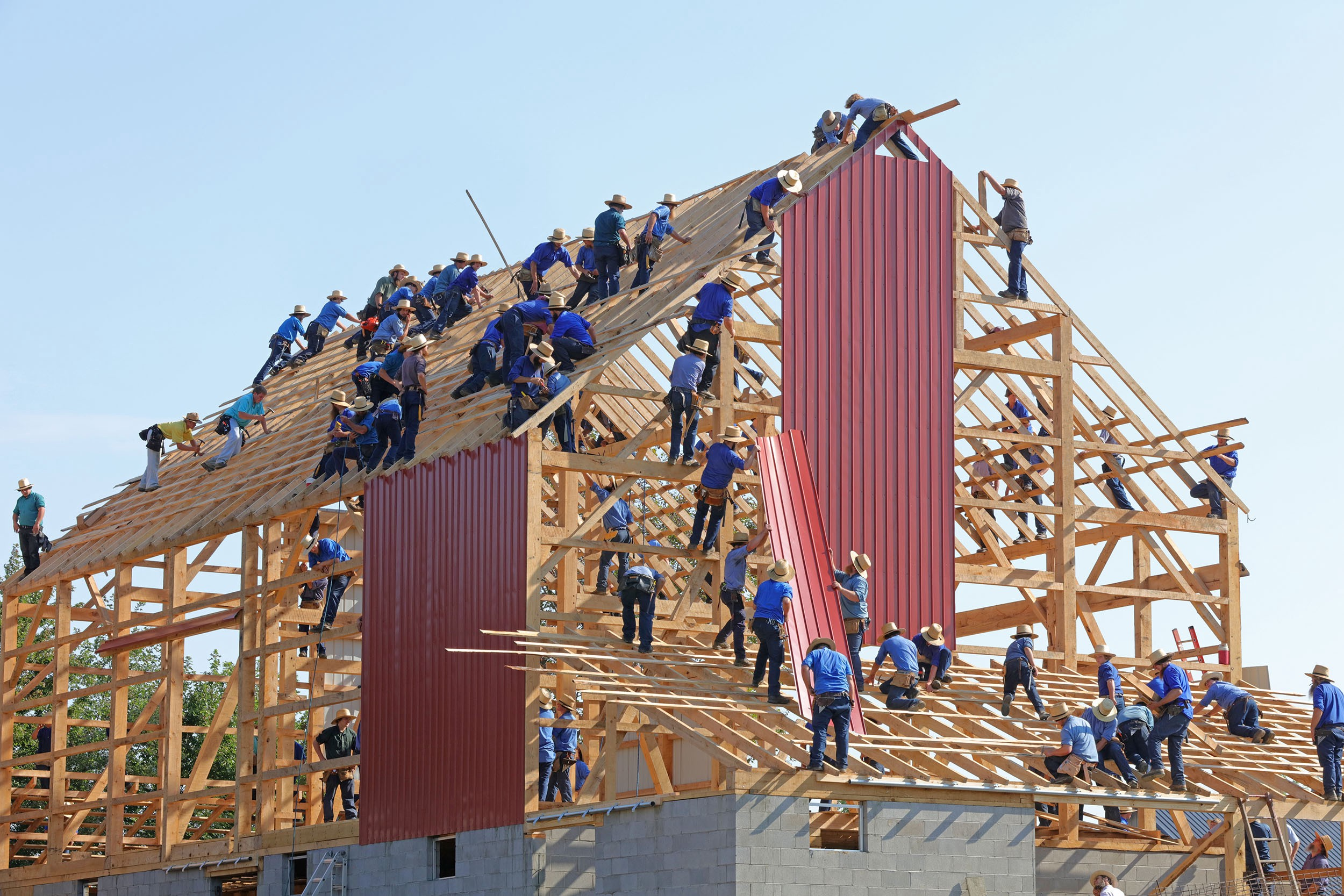 a large group of people building a house together, each helping with a different aspect