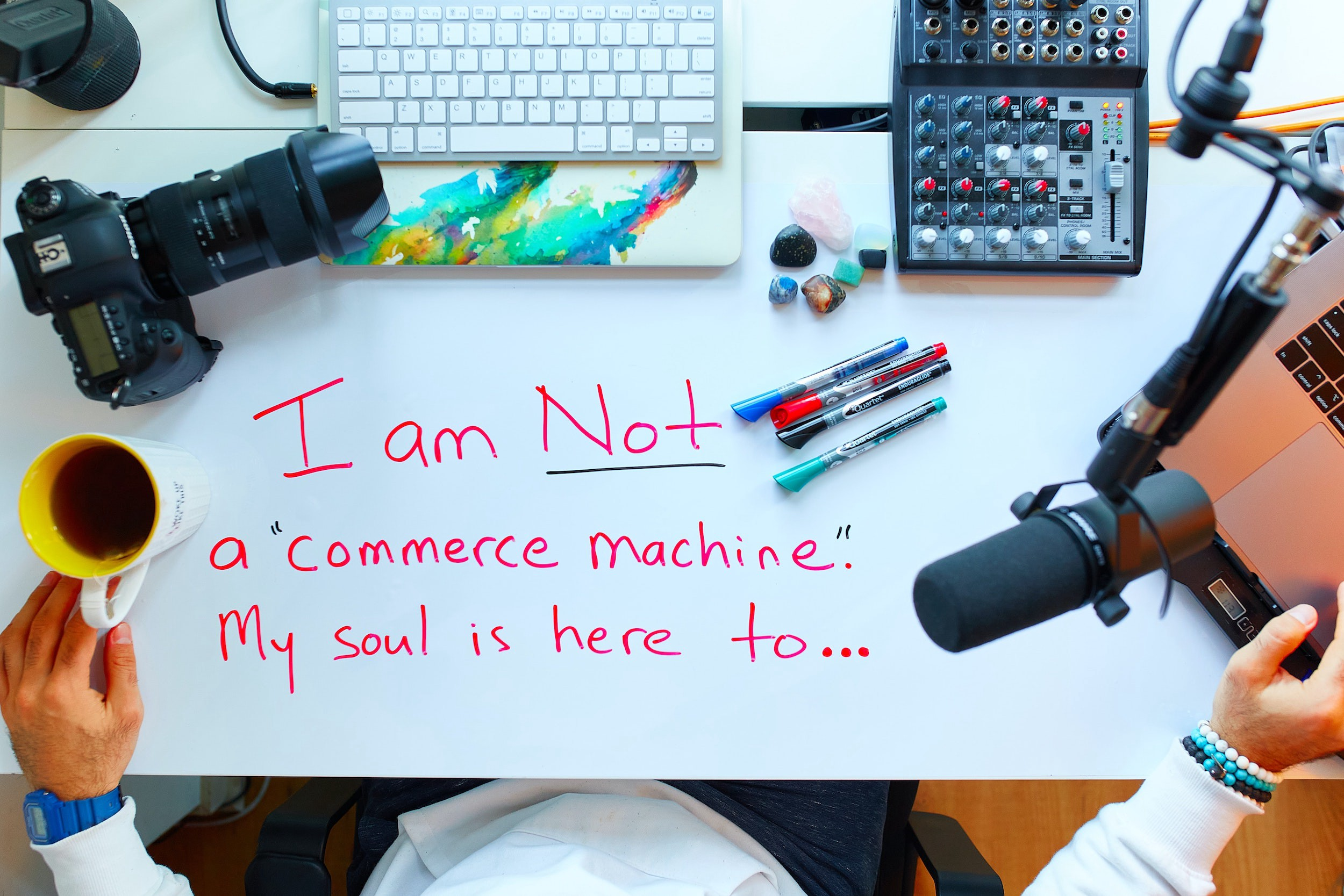 """Podcaster desk with """"I am not a commerce machine. My should his here to…"""" written on it."""