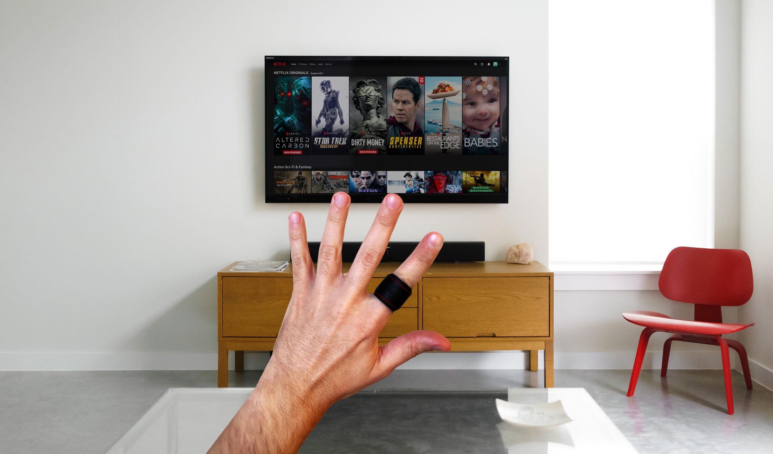 Digital rendering of how the device may look on the index finger. A black ring with RGB LED stripes for controlling Netflix.