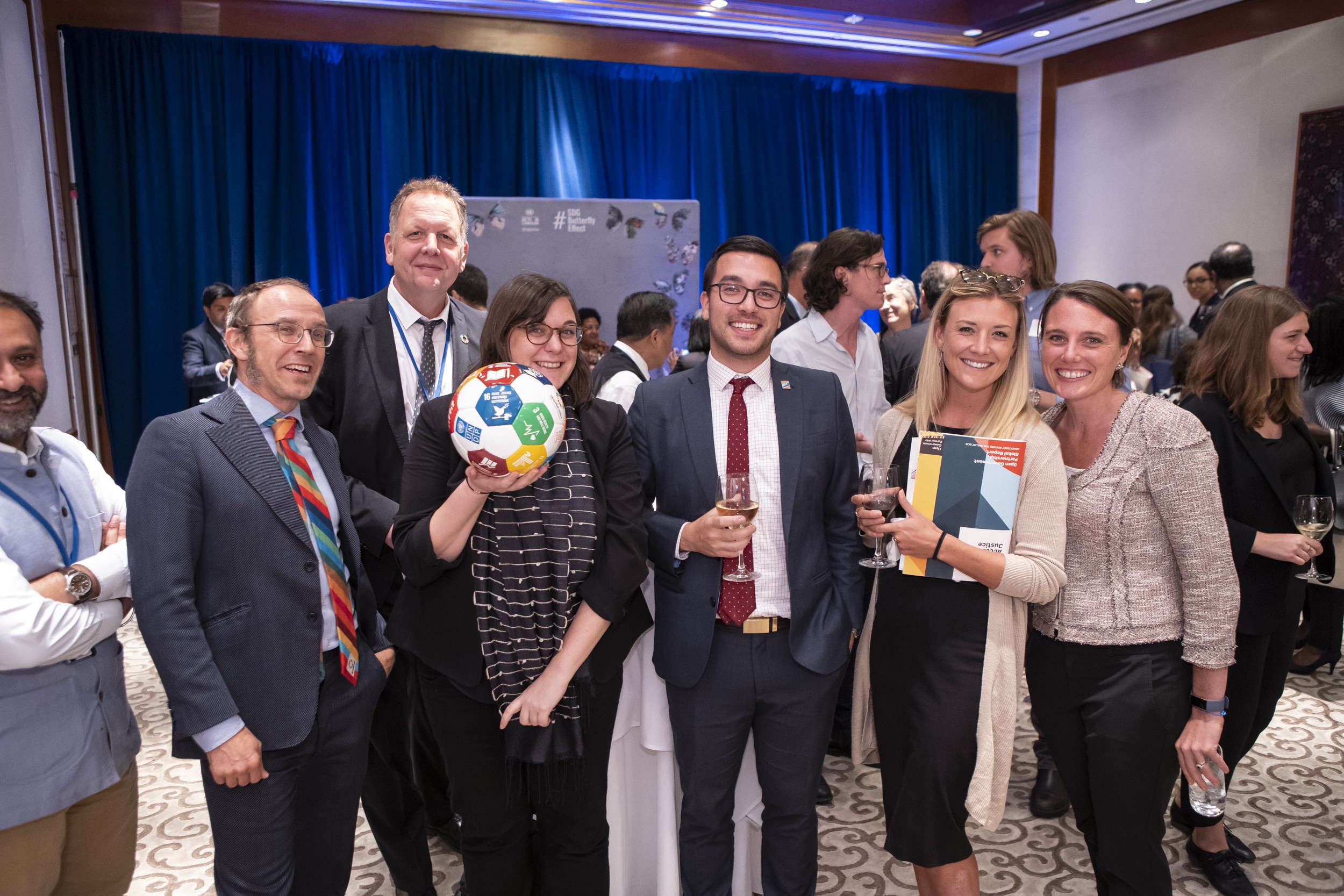 A group of six individuals at the evening reception, one of which is holding an SDG soccer ball.