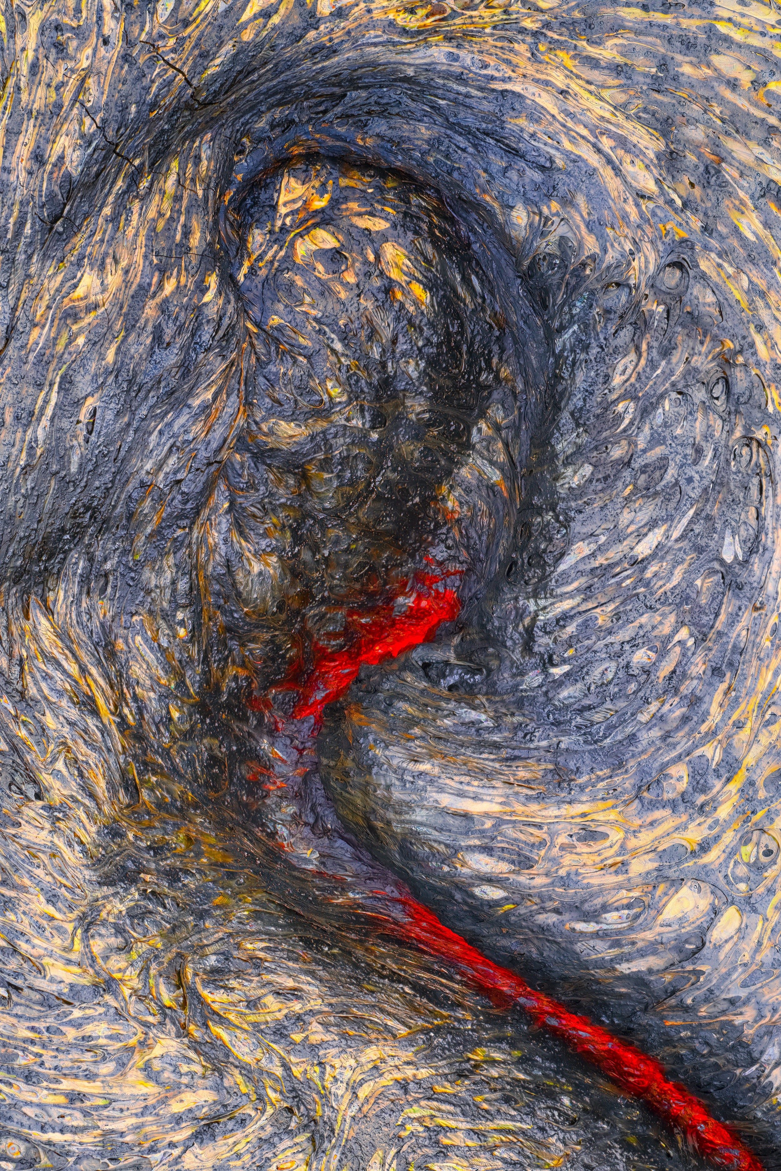 A photo of melting lava shows a yellow and black ground with glowing red lava shown in a wiggling line, glowing below
