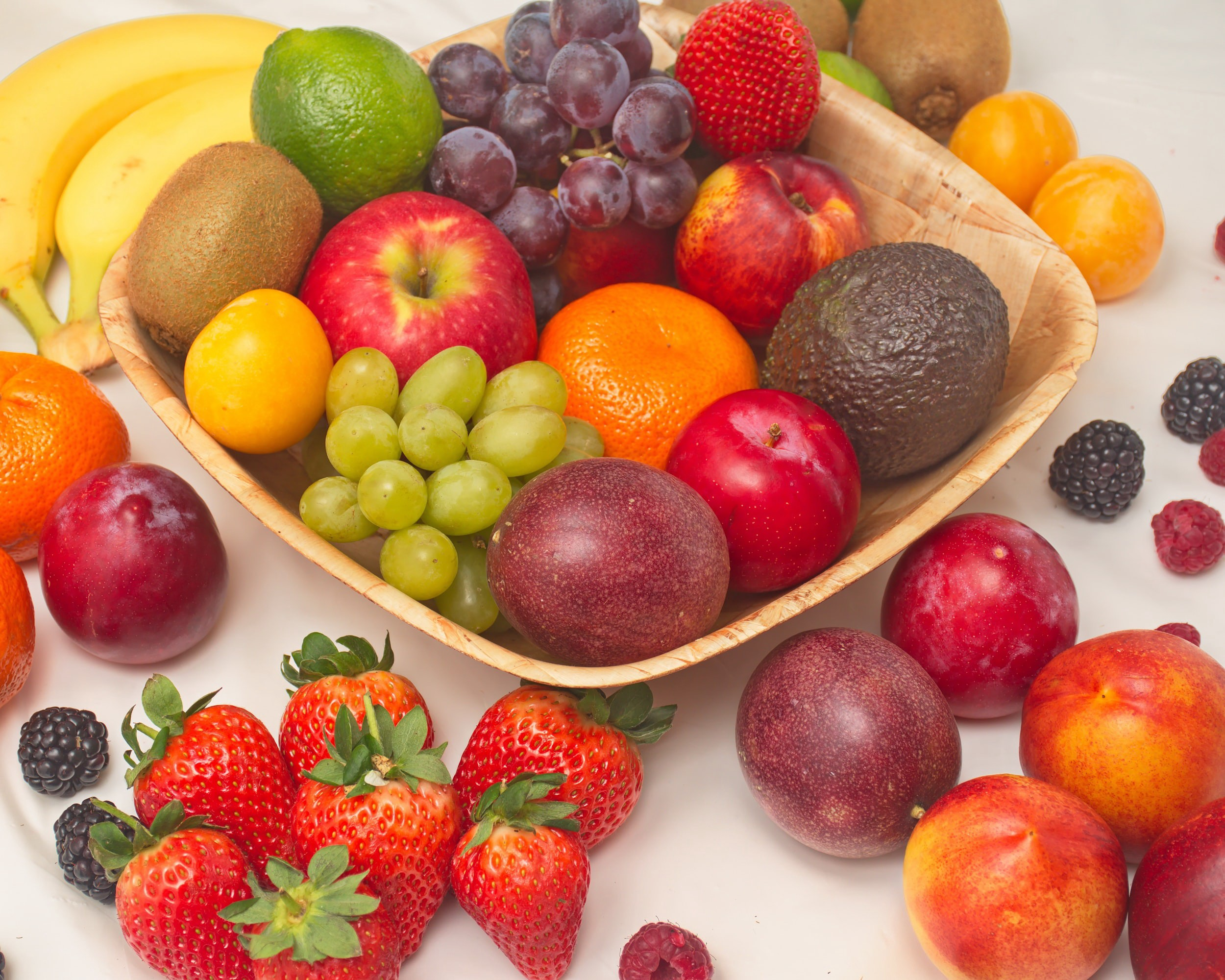 selection of colorful fresh fruit in wooden bowl strawberries grapes plumbs avocado berries