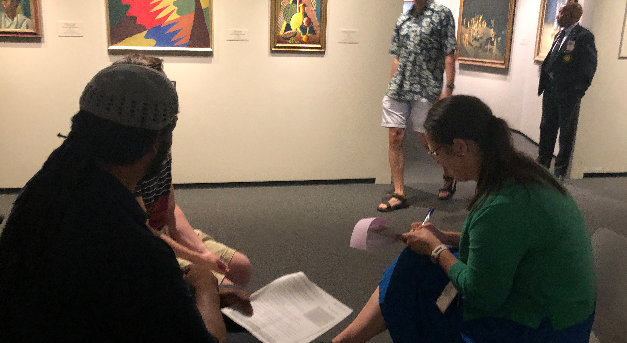 Museum staff members interviewing a visitor in a gallery filled with early modern art works.