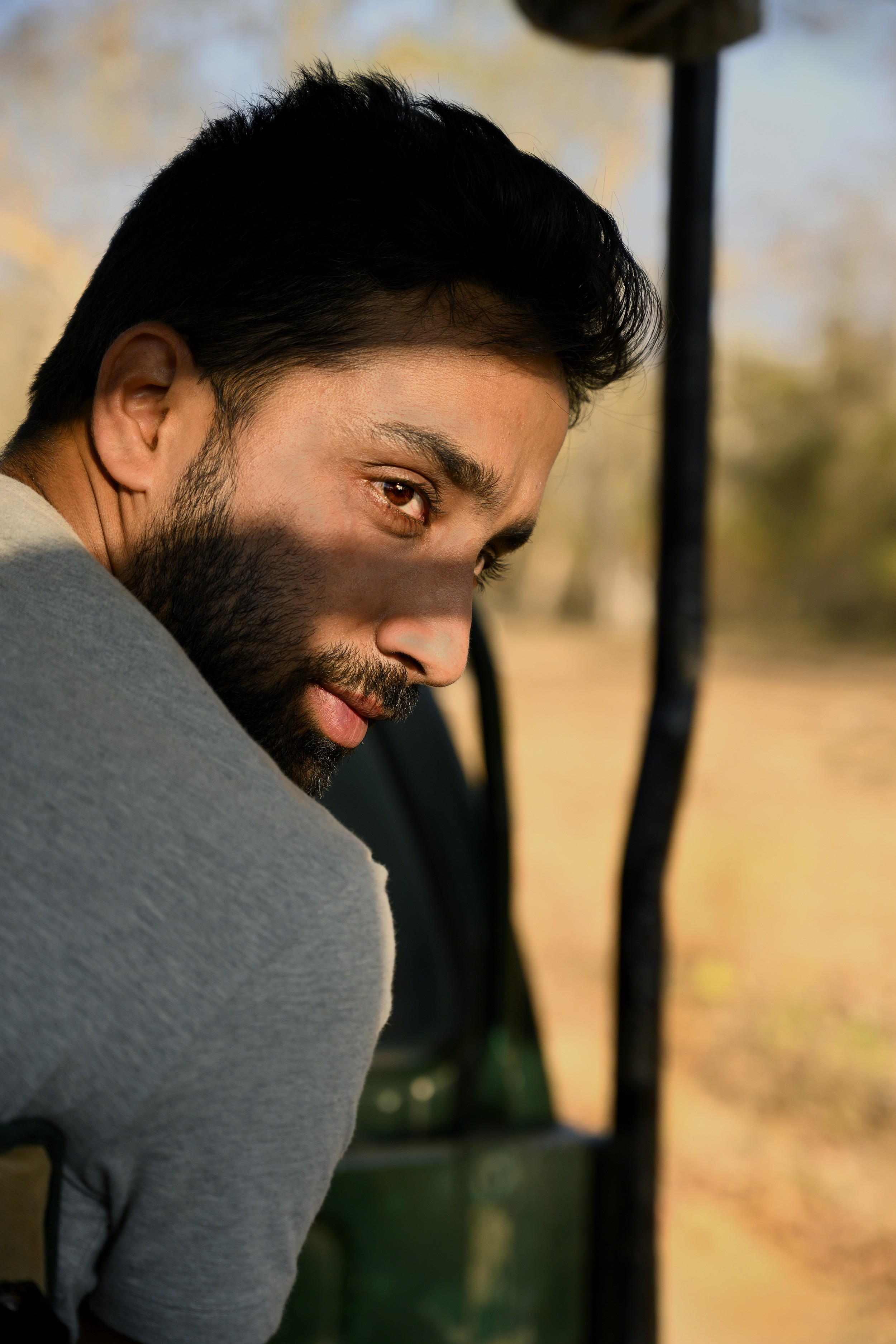 Mithun, outside in the desert, seen in profile from over his shoulder, shadows falling across his face.