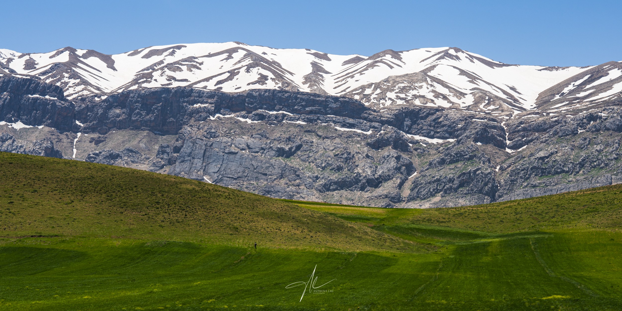 The many layers of colours along the road in the Zagros Mountains—from the blue sky, snow top summit, to green pasture.