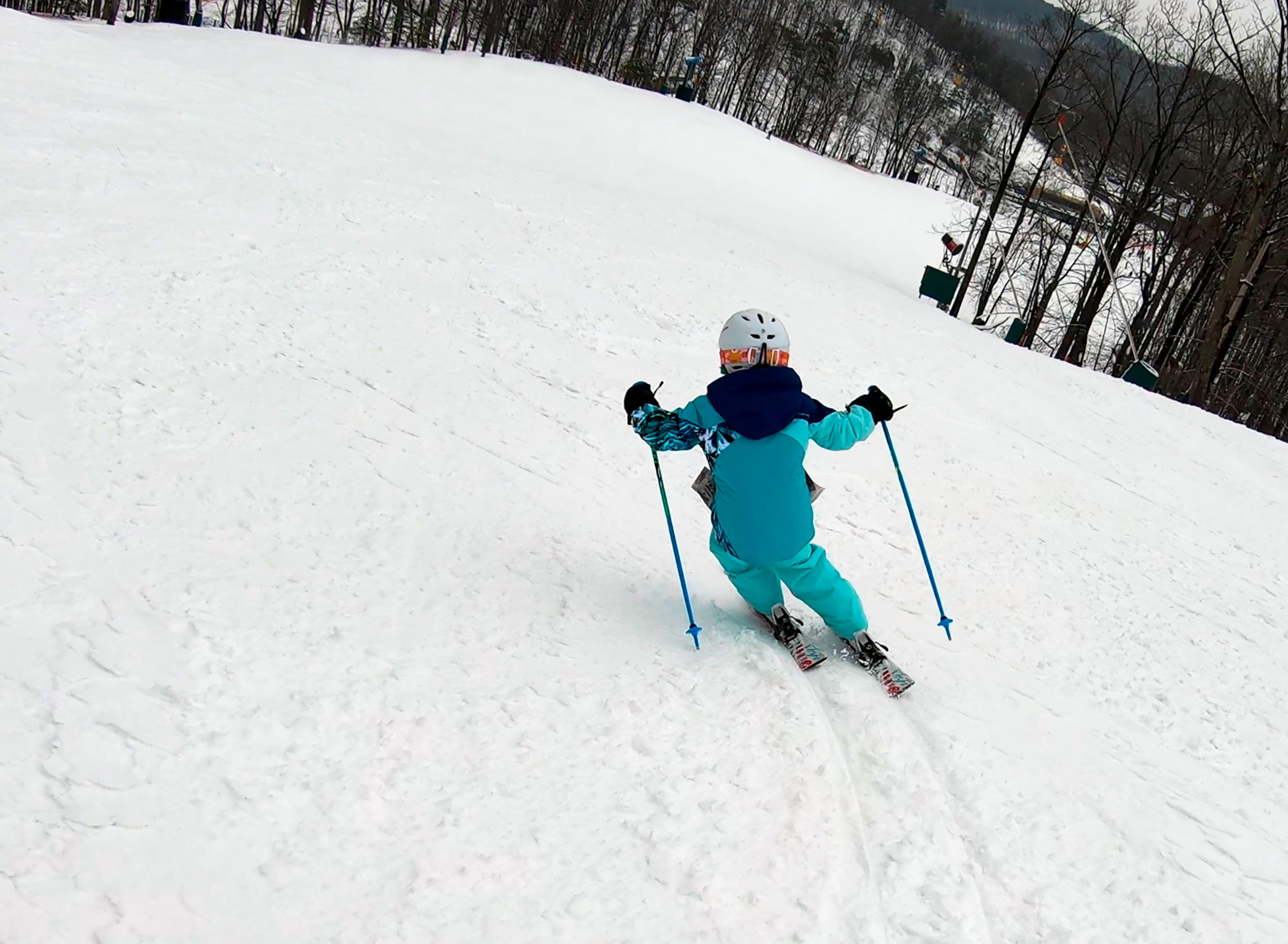 My youngest daughter carving down the mountain. The railroad tracks left by her skis are very clear on the packed snow.
